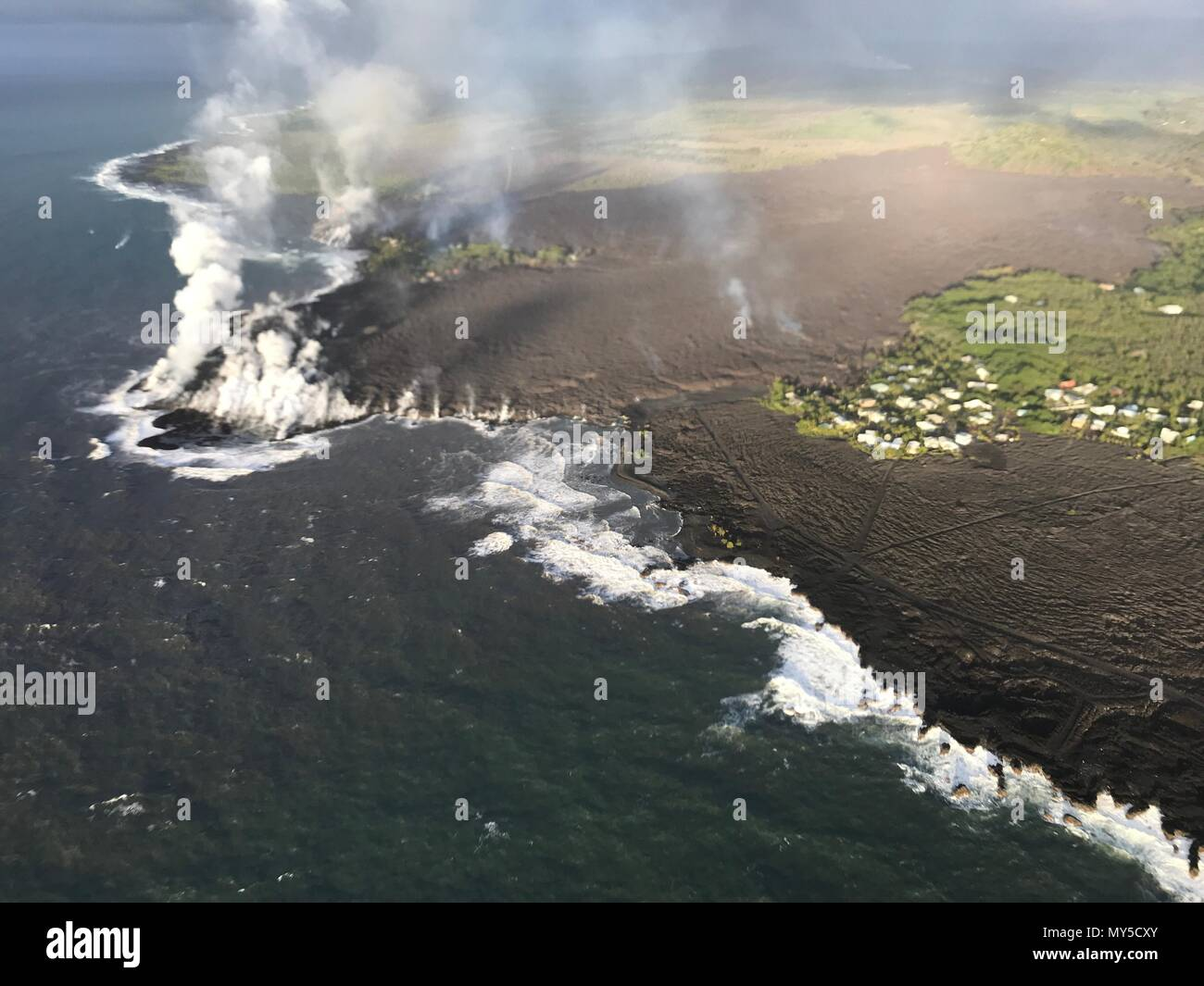 Lava flows into Kapoho Bay destroying forest and homes in the Vacationland area caused by the eruption of the Kilauea volcano June 5, 2018 in Hawaii. The recent eruption continues destroying homes, forcing evacuations and spewing lava and poison gas on the Big Island of Hawaii. - Stock Image
