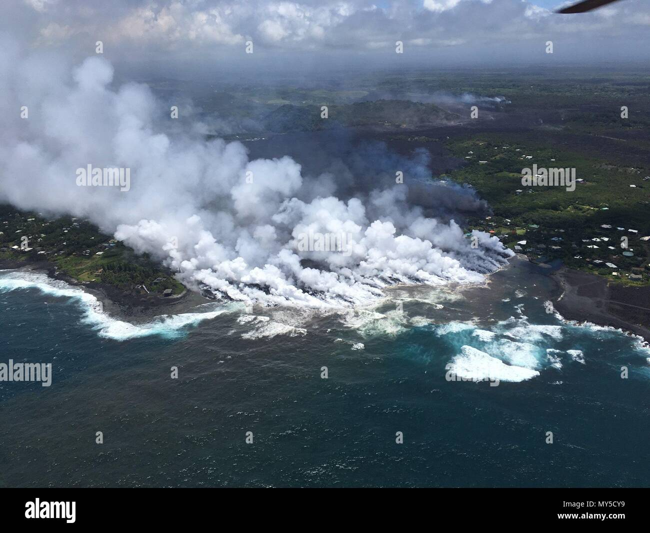 Lava flows into Kapoho Bay destroying forest and homes in the Vacationland area caused by the eruption of the Kilauea volcano June 4, 2018 in Hawaii. The recent eruption continues destroying homes, forcing evacuations and spewing lava and poison gas on the Big Island of Hawaii. - Stock Image