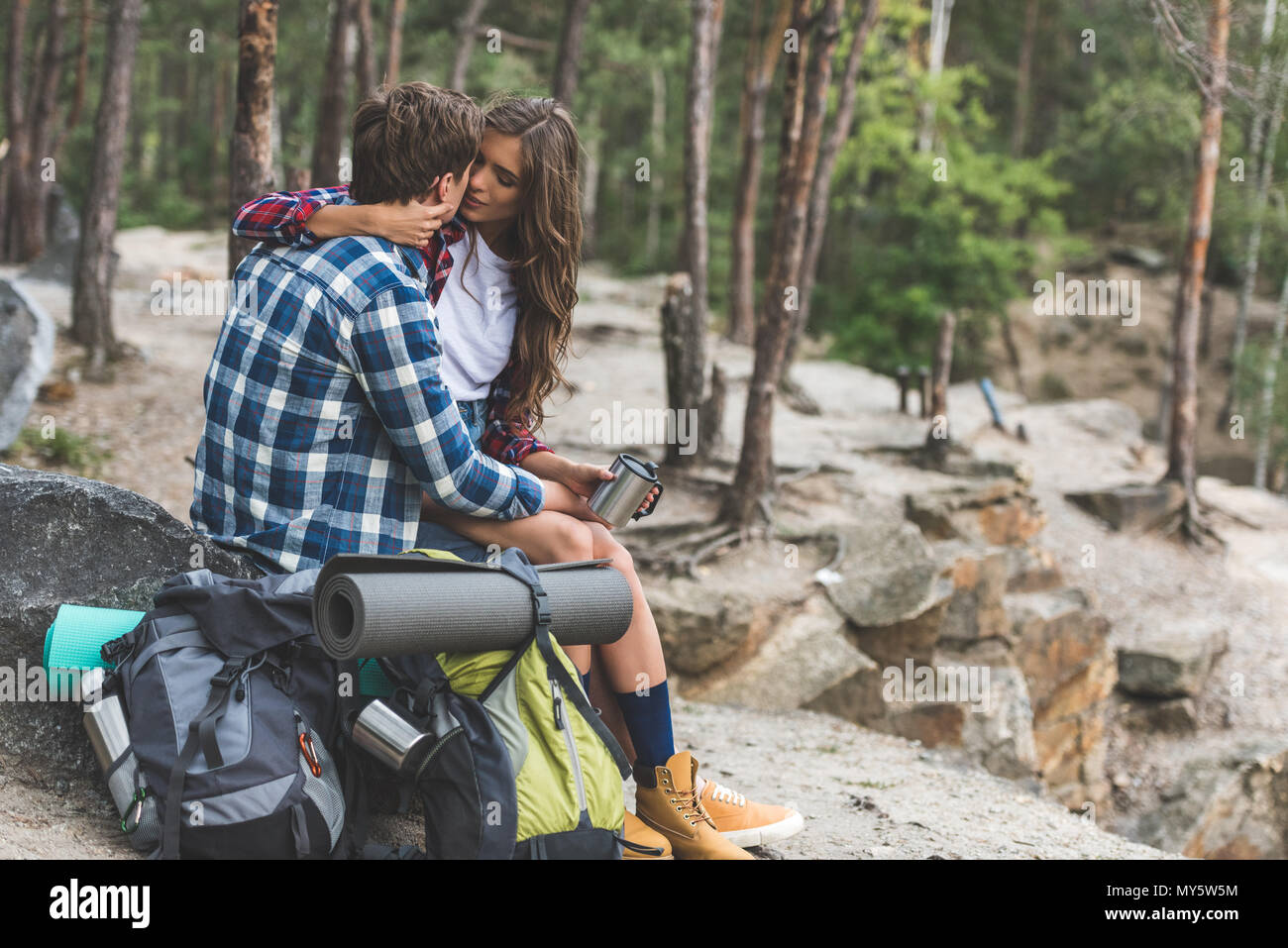 active couple kissing while having trip in forest - Stock Image