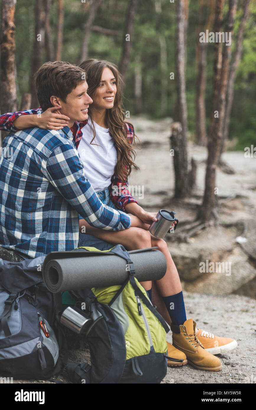 young couple with backpacks relaxing in forest while having hiking trip - Stock Image