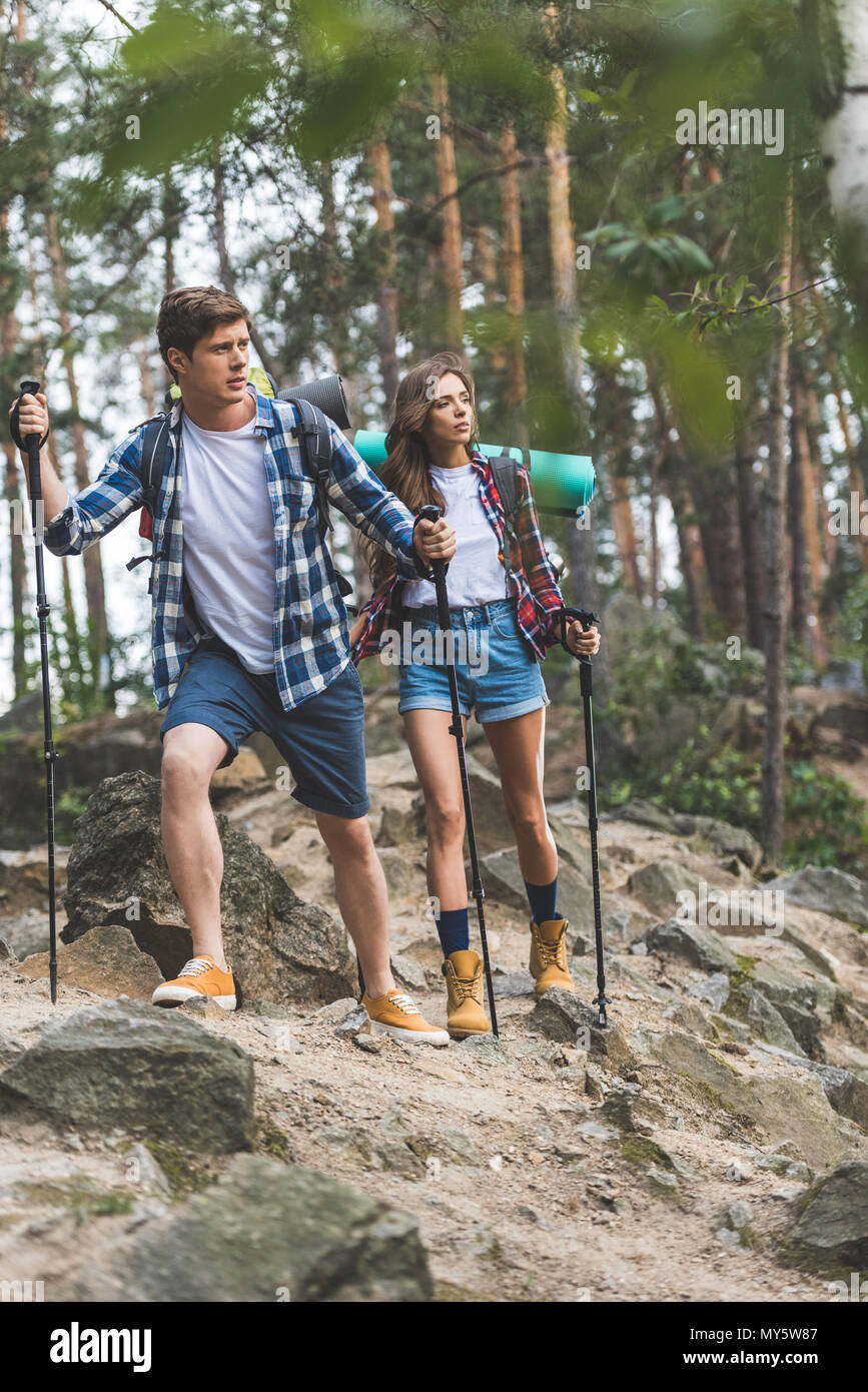 young active couple with trekking poles having trip - Stock Image