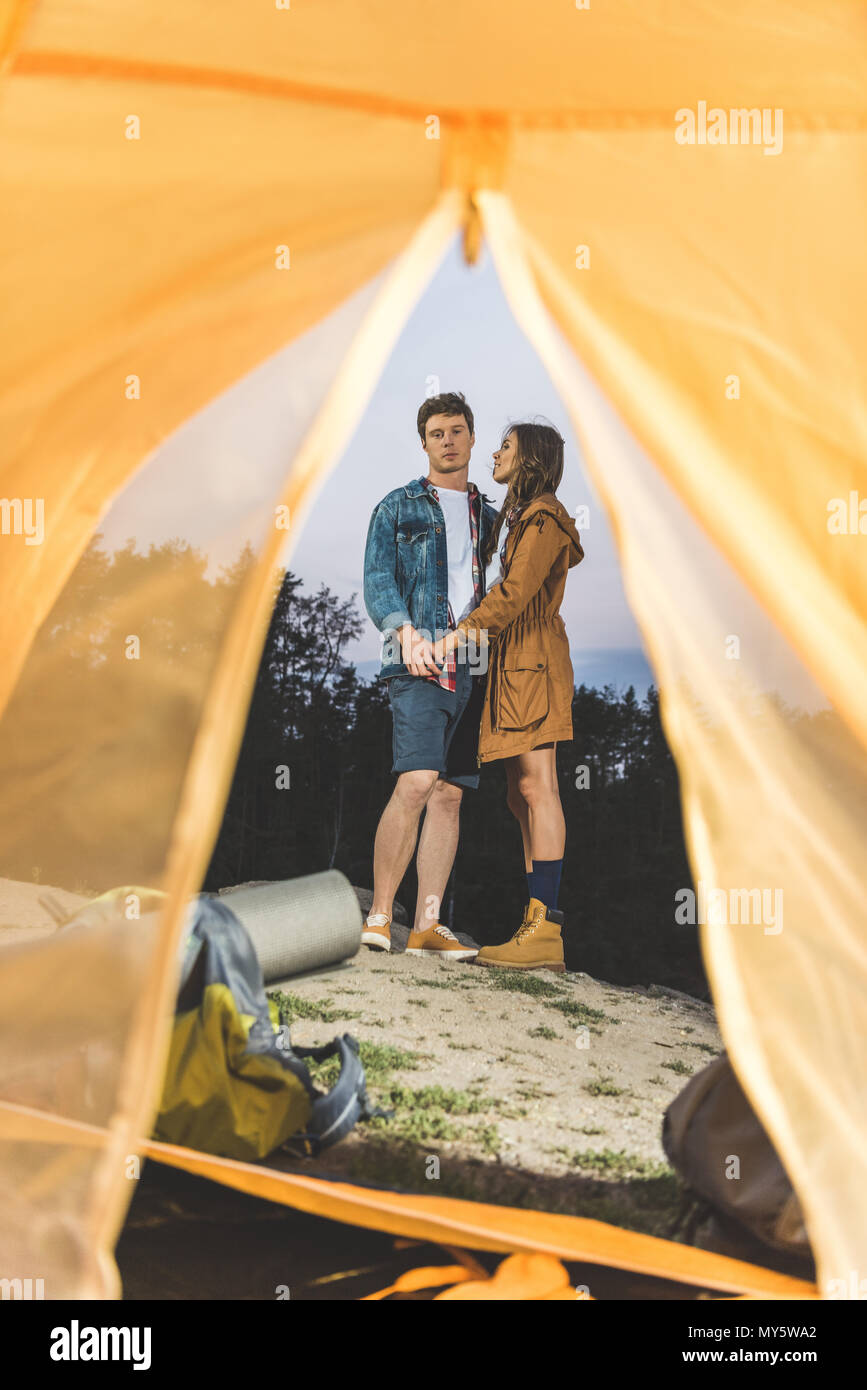 view from tent on young couple on hiking trip holding hands - Stock Image