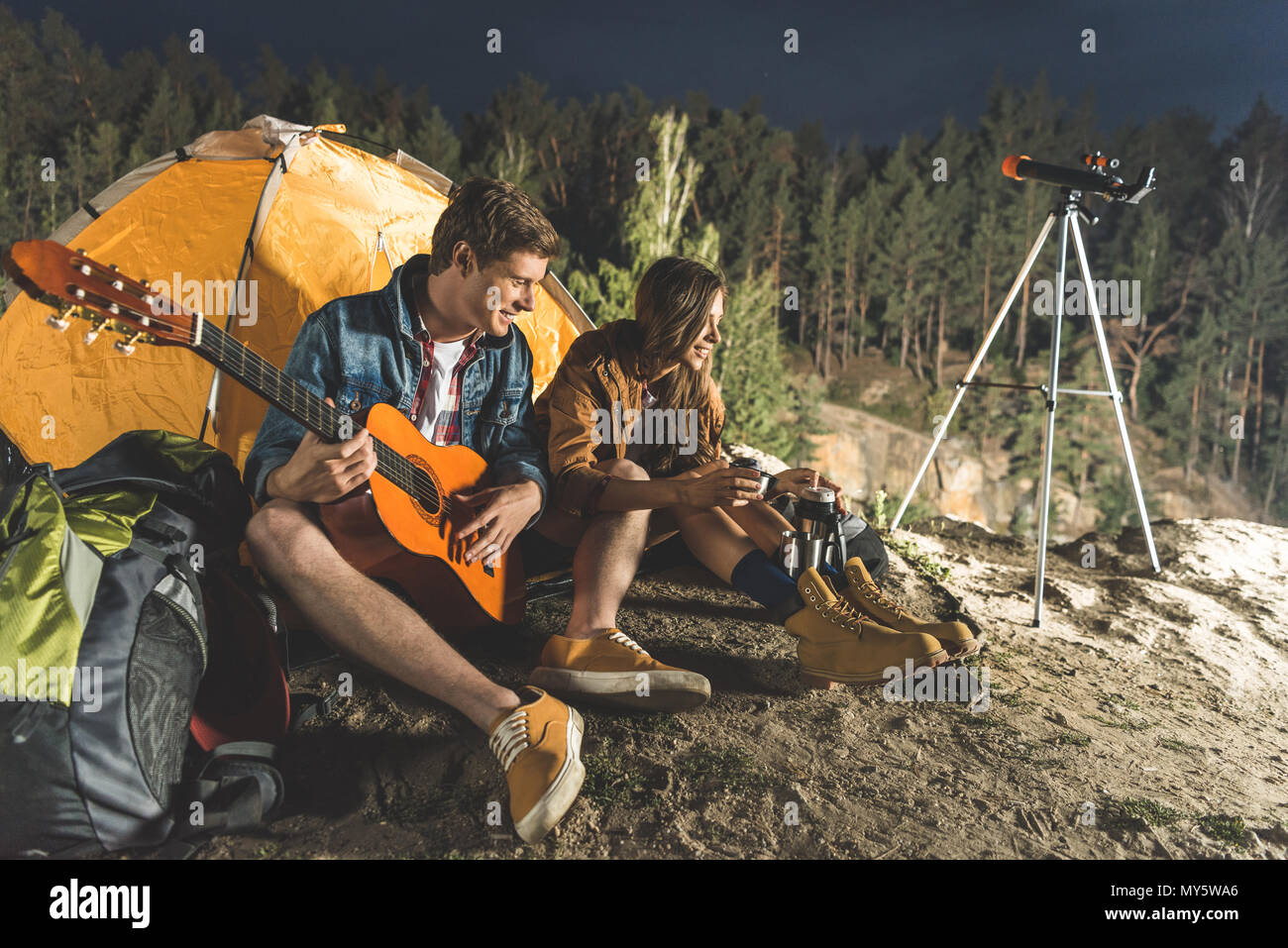 young man playing guitar for beautiful happy girlfriend in hiking trip - Stock Image