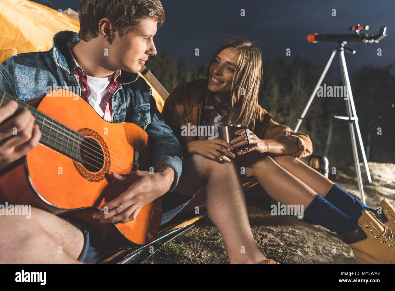 happy man playing guitar for girlfriend in hiking trip - Stock Image
