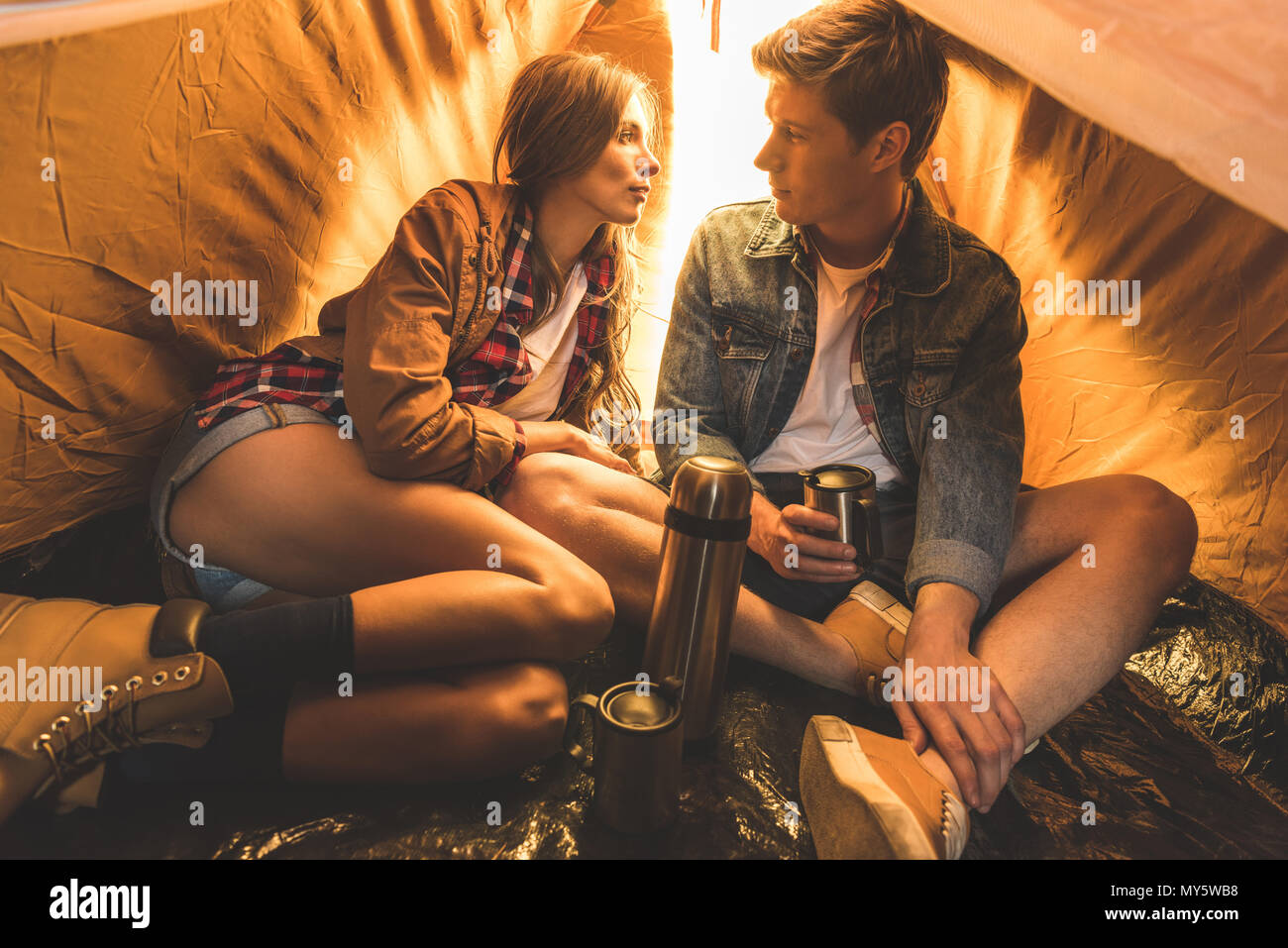 young couple sitting in tent together with hot drink looking at each other - Stock Image