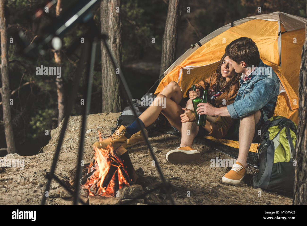 young couple on hiking trip drinking beer in tent - Stock Image