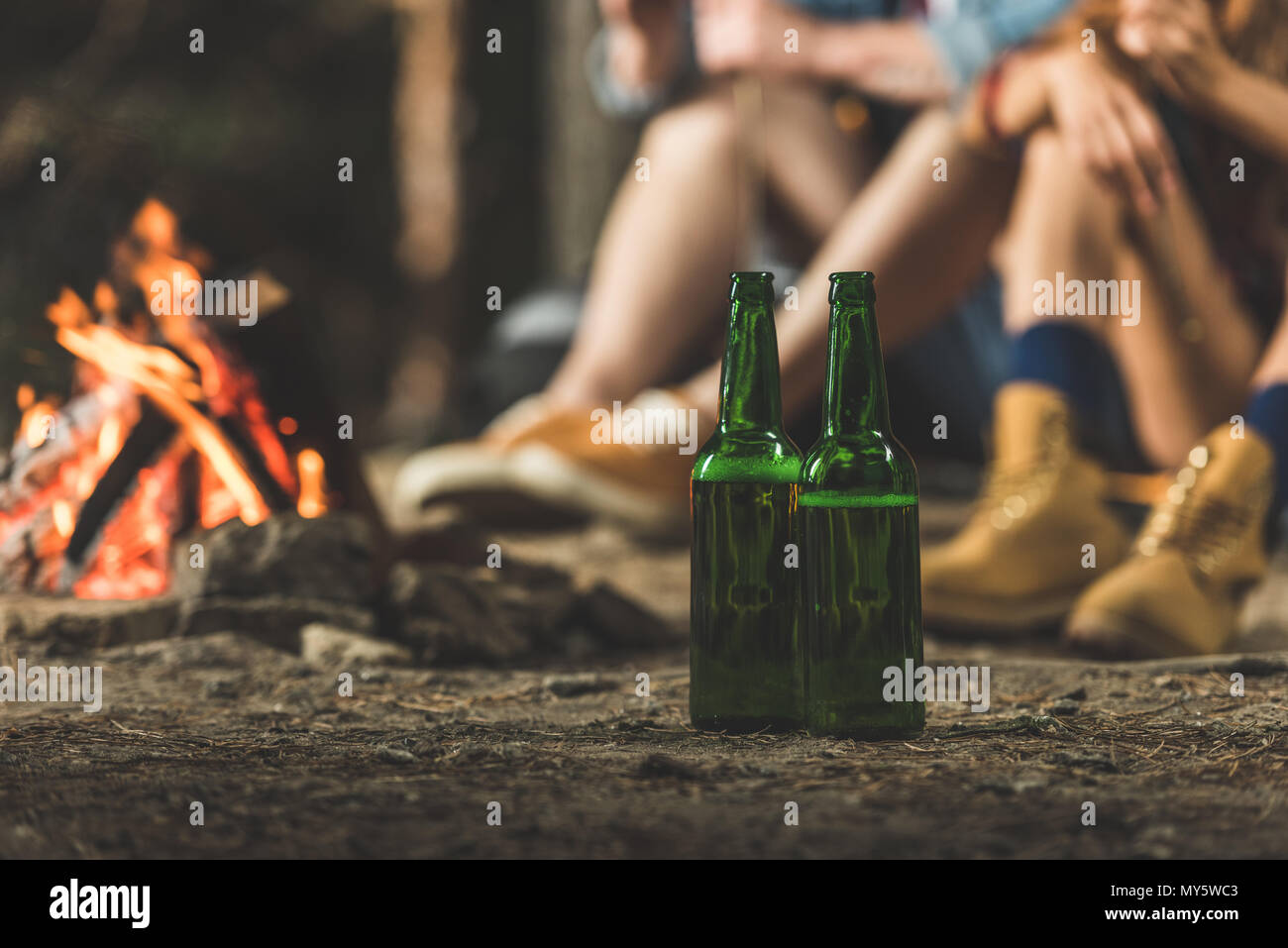 bottles of beer in hiking camp next to bonfire - Stock Image