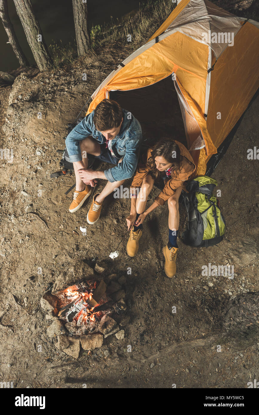 top view of couple roasting marshmallow on sticks in camping trip - Stock Image