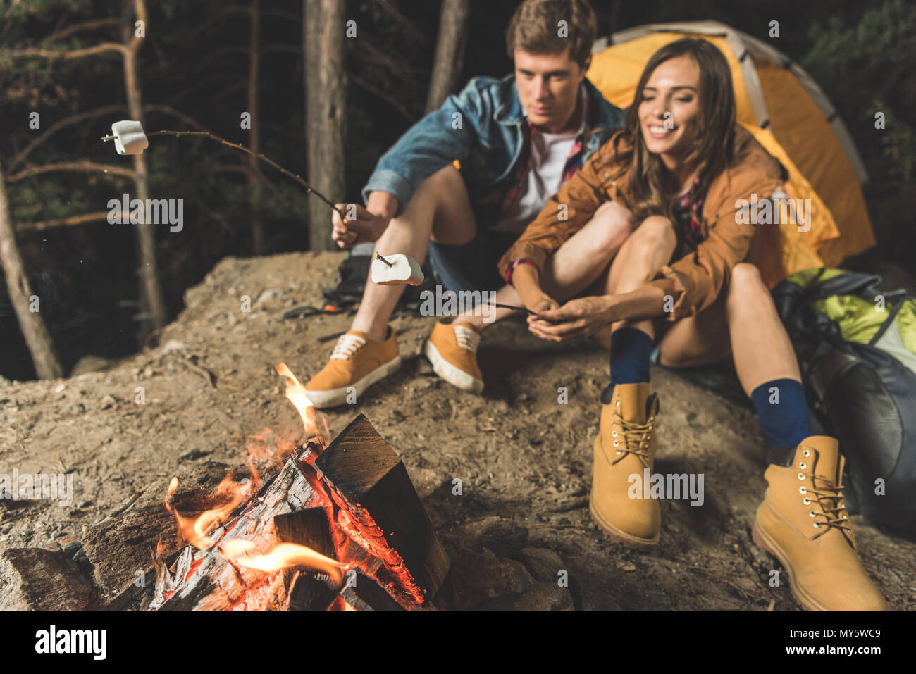 beautiful couple roasting marshmallow on sticks in camping trip - Stock Image