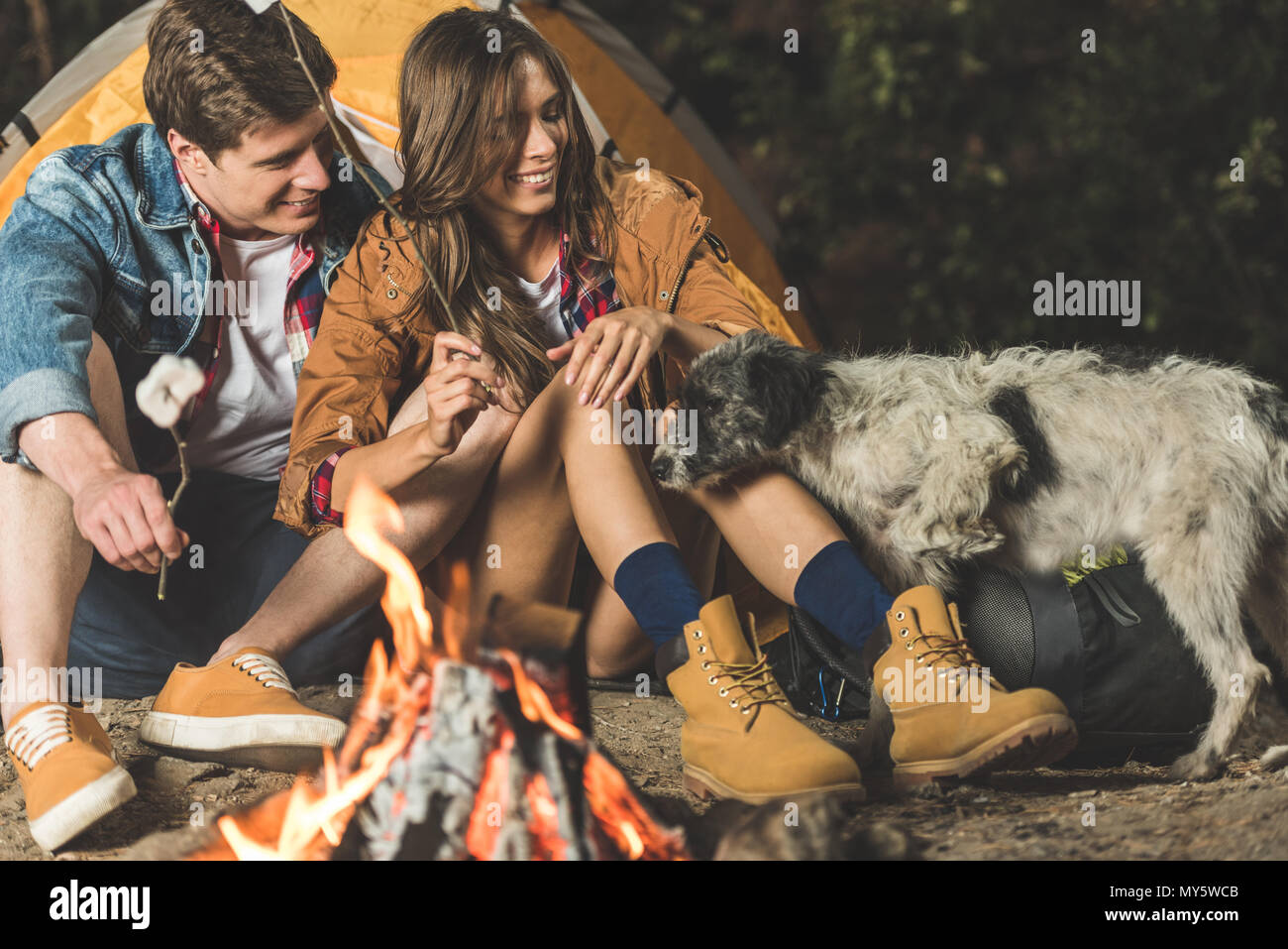 young happy couple on hiking trip with old dog roasting marshmallow - Stock Image