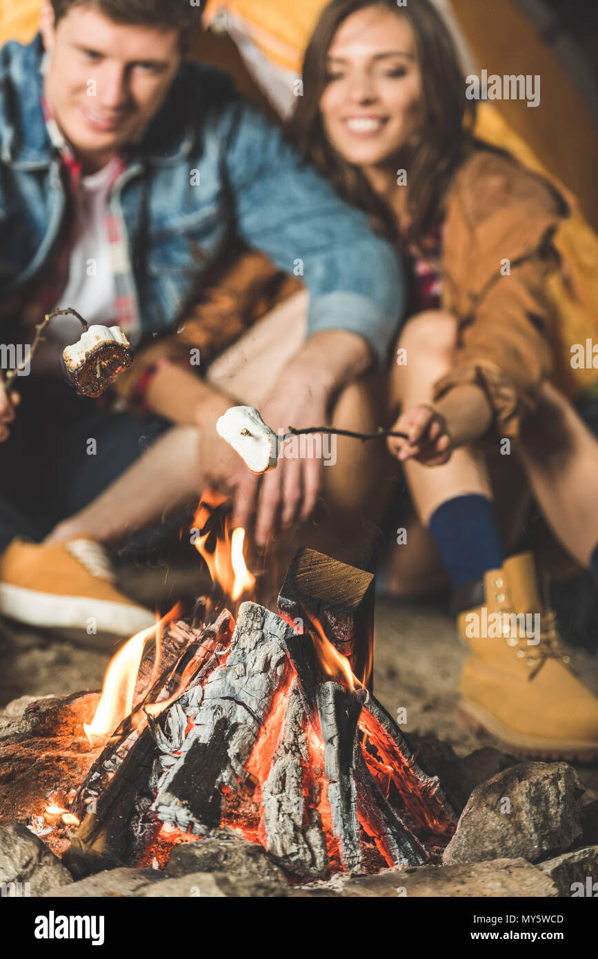 young couple roasting marshmallow on sticks in camping trip - Stock Image