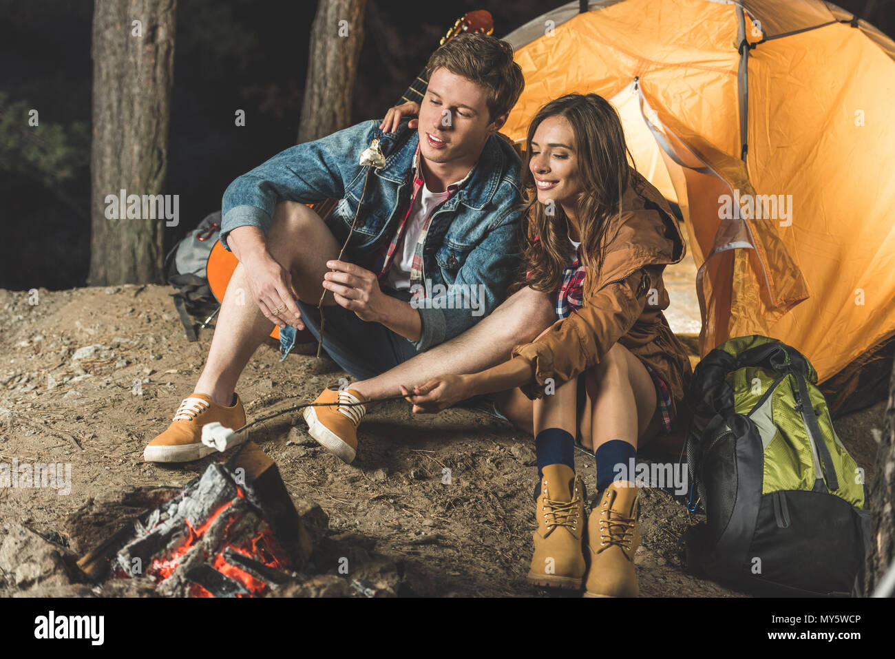 couple roasting marshmallow on sticks in camping trip - Stock Image