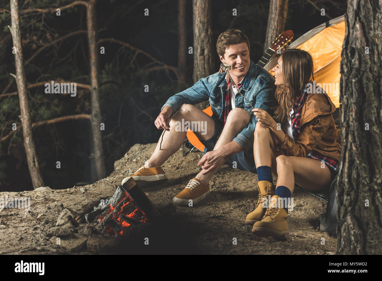 happy couple roasting marshmallow on sticks in camping trip - Stock Image