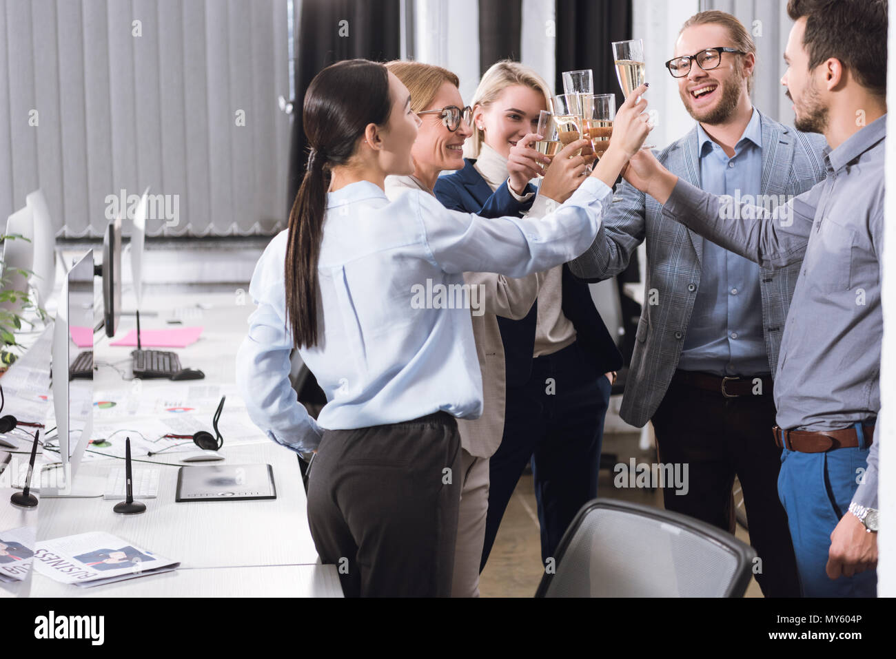 group of businesspeople clinking glasses of champagne in office - Stock Image