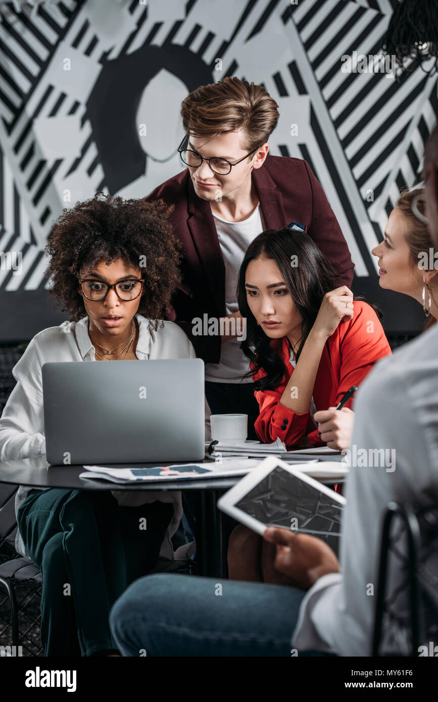 group of young interested business partners looking at laptop together - Stock Image
