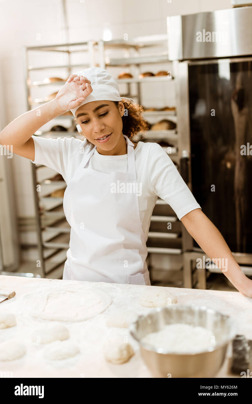 overworked female baker wiping sweat from forehead at baking manufacture - Stock Image