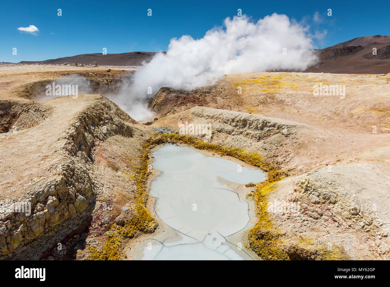 The volcanic activity of Sol de Mañana in Bolivia between Chile and the Uyuni Salt Flat. Mud pits and fumaroles with water vapor trails in the Andes. - Stock Image