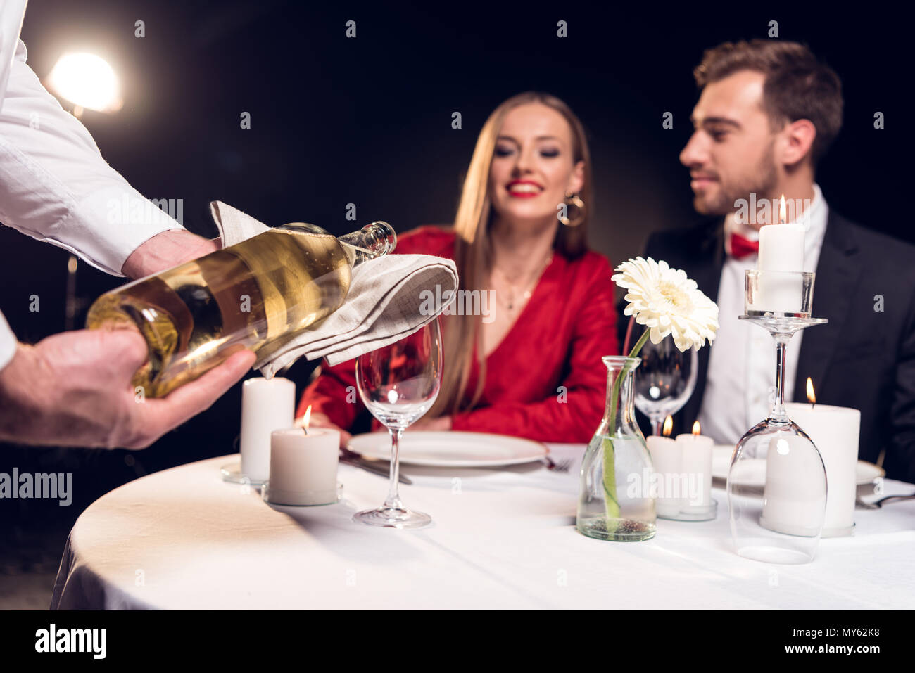 waiter pouring wine while couple having romantic date in restaurant on valentines day - Stock Image