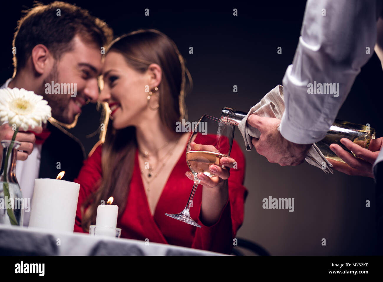 waiter pouring wine while smiling couple having romantic date in restaurant on valentines day - Stock Image