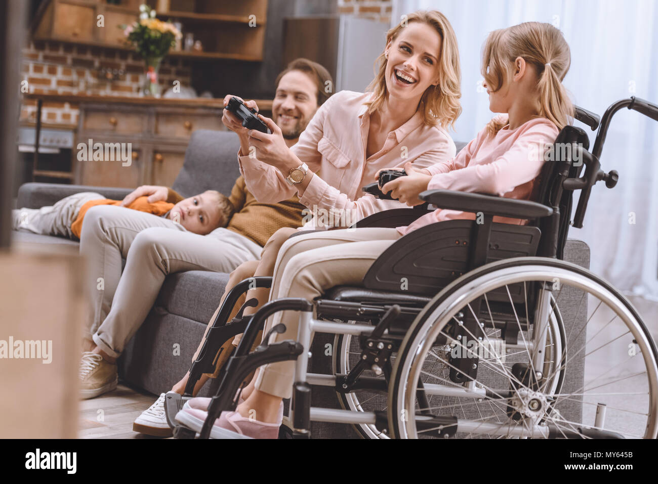 family with disabled child in wheelchair playing with joysticks together at home - Stock Image