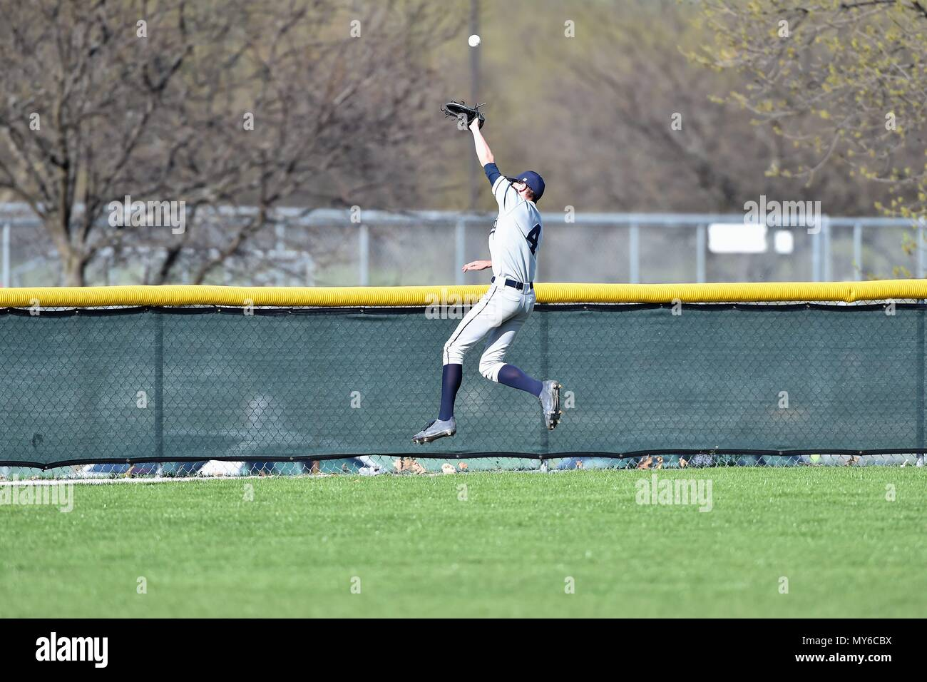 Center fielder making a leaping effort for a drive that eluded his grasp and fell for a triple. USA. - Stock Image
