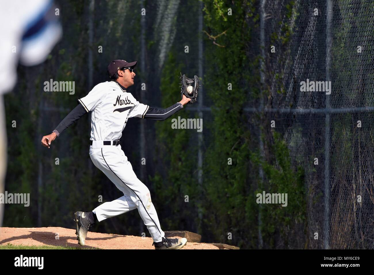 Right fielder making a one-handed running catch of a fly ball in the opposing bullpen. USA. - Stock Image