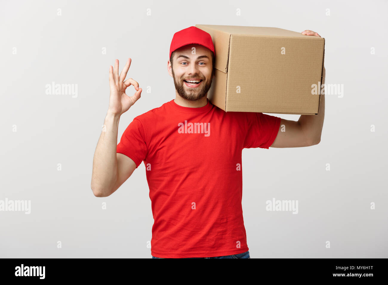 Young delivery man in red cap standing with parcel post box isolated over white background showing okay gesture. Stock Photo