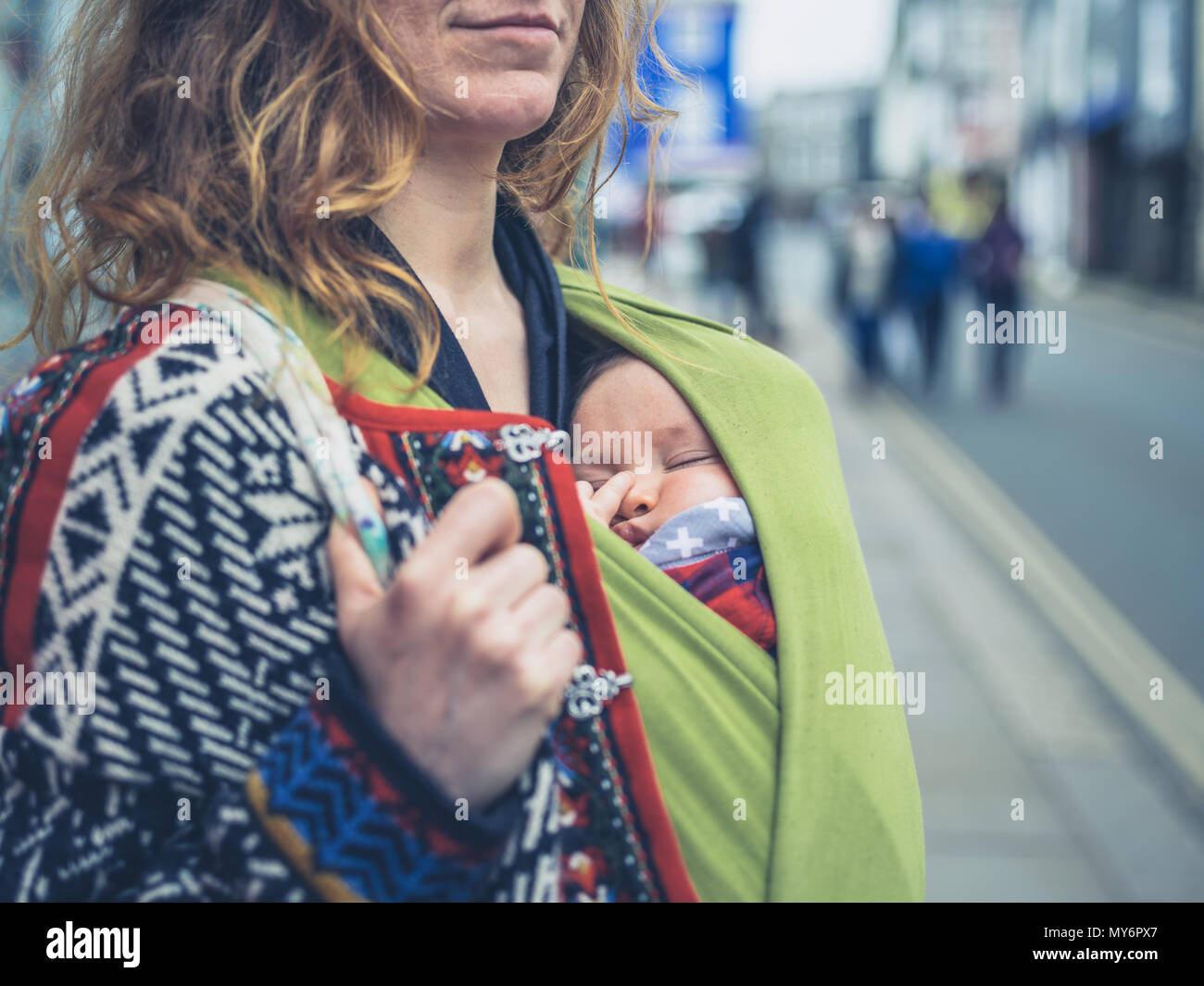 A young mother in the street with her baby in a carrier sling - Stock Image