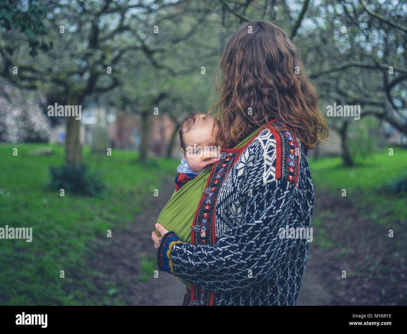 A young mother is standing in the park with her baby in a carrier sling - Stock Image