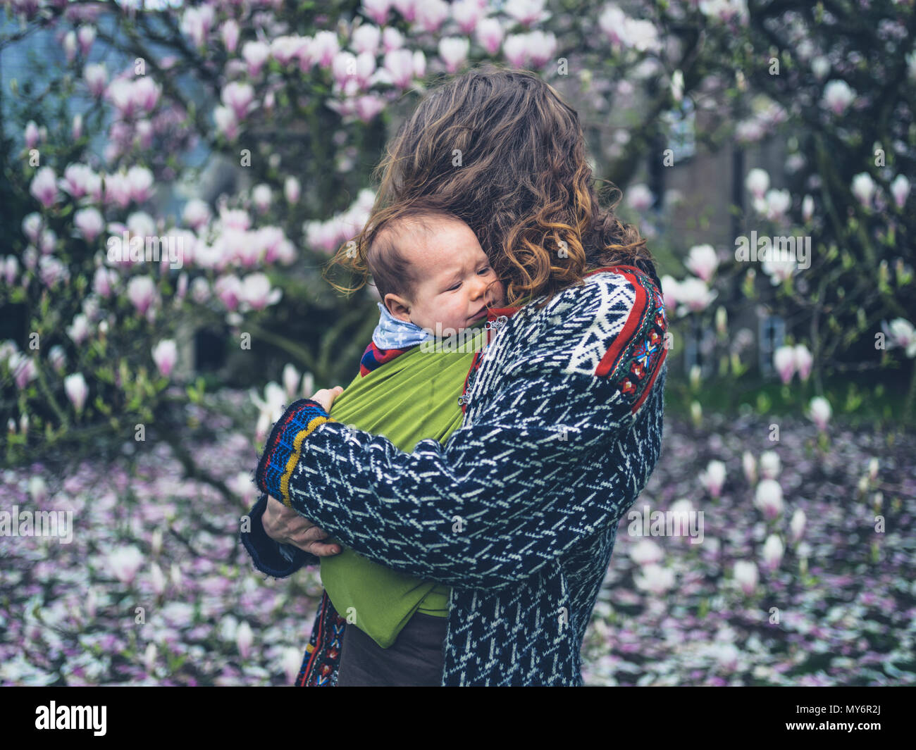 A Young Mother With Her Crying Baby In A Sling Is Standing By A