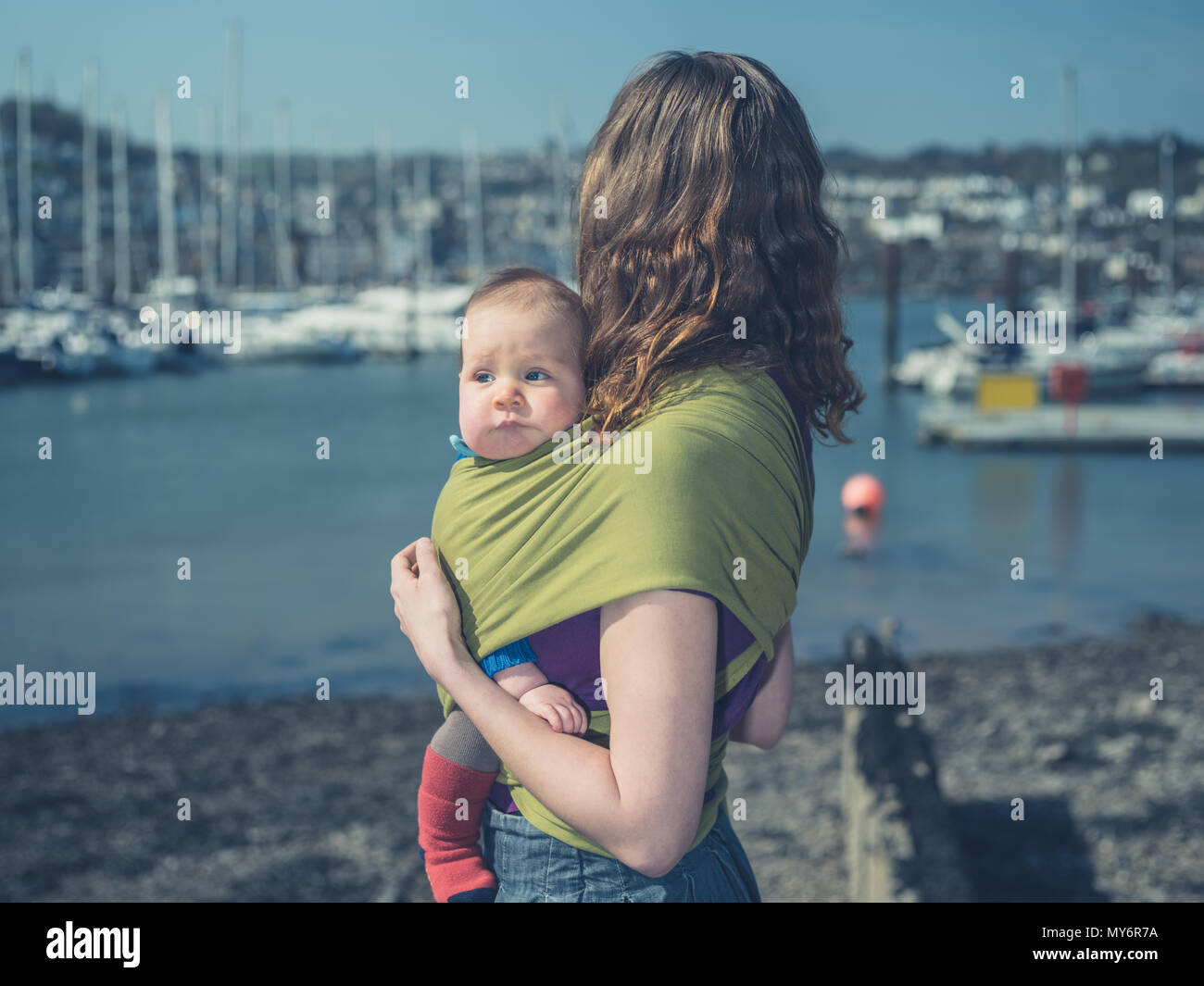 A young mother is standing in a harbor on a sunny day with her baby in a sling - Stock Image
