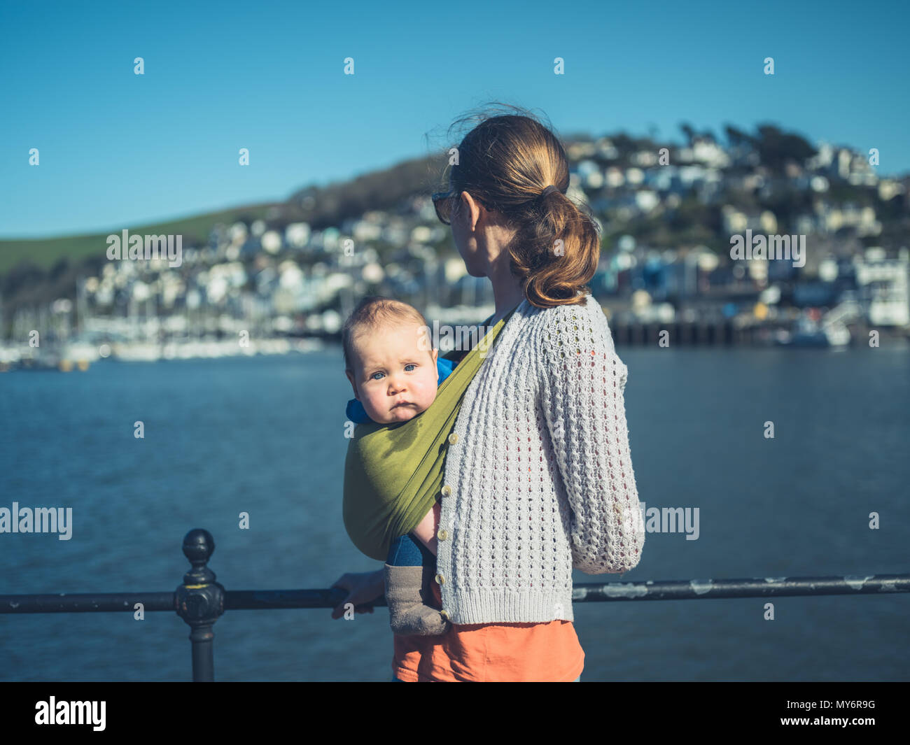 A young mother is standing by the river in a small village with her baby in a sling - Stock Image