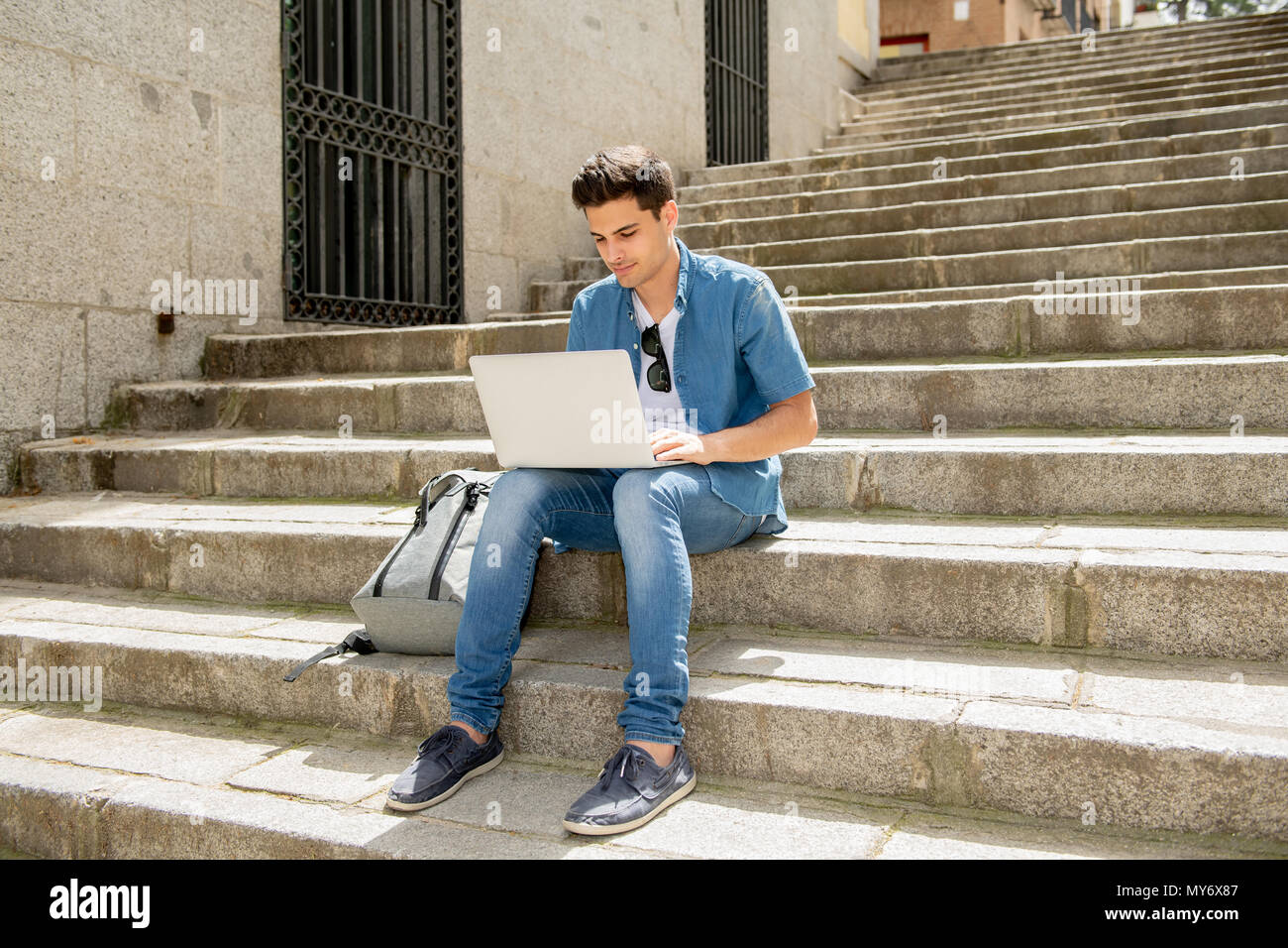 5e983173086 Young handsome modern man in smart casual wear using laptop computer in the  city sitting on the stairs outdoor. In student