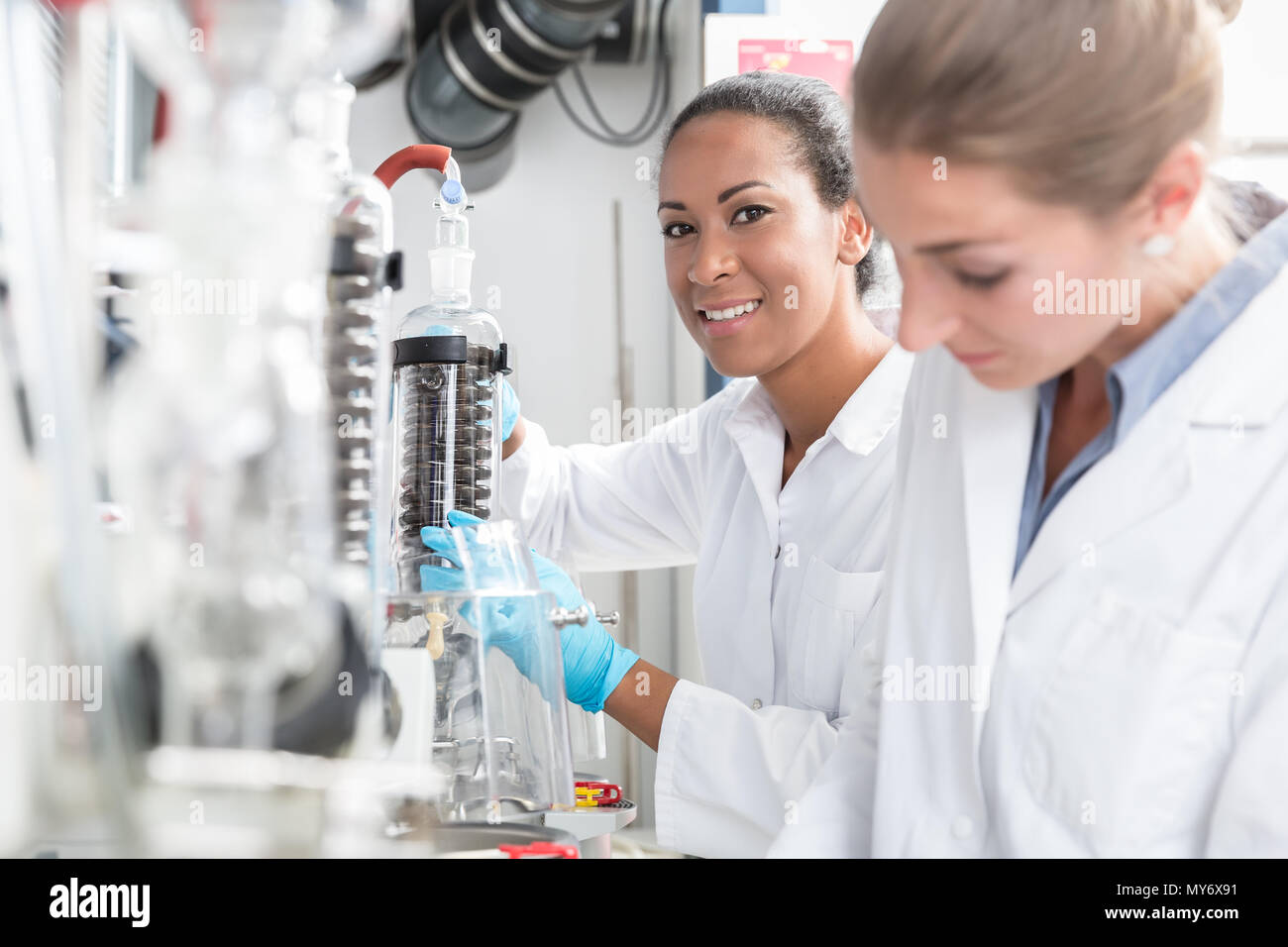 Group of scientists with gloves and gowns in laboratory - Stock Image