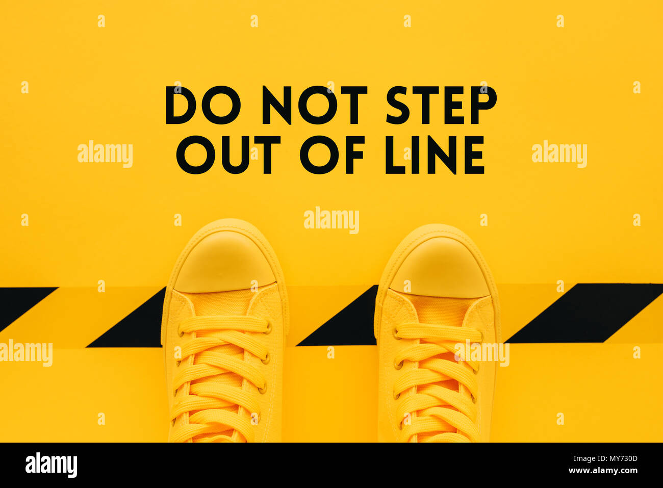 Do not step out of line, person in yellow sneakers breaking the rules and acting in an inappropriate or unacceptable way - Stock Image