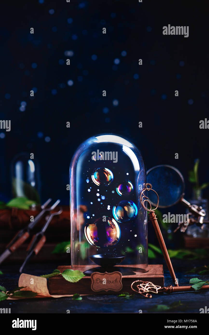 Soap bubbles under a glass dome with a DIY bubble wand. Preserving fleeting summer and childhood concept with copy space on a dark background - Stock Image