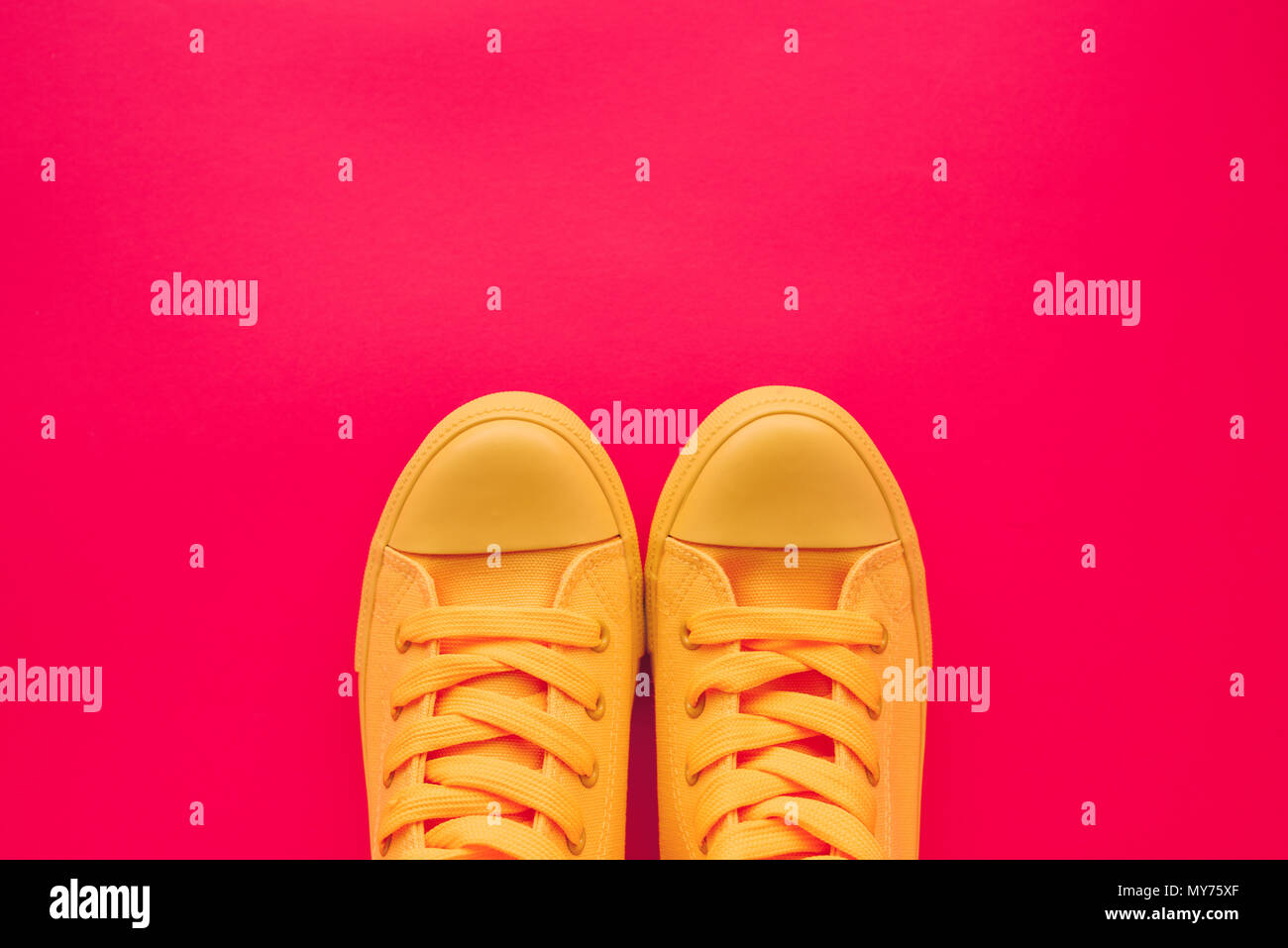 64fddd5333fc27 Yellow canvas shoes sneakers on neon pink background, top view with copy  space - Stock