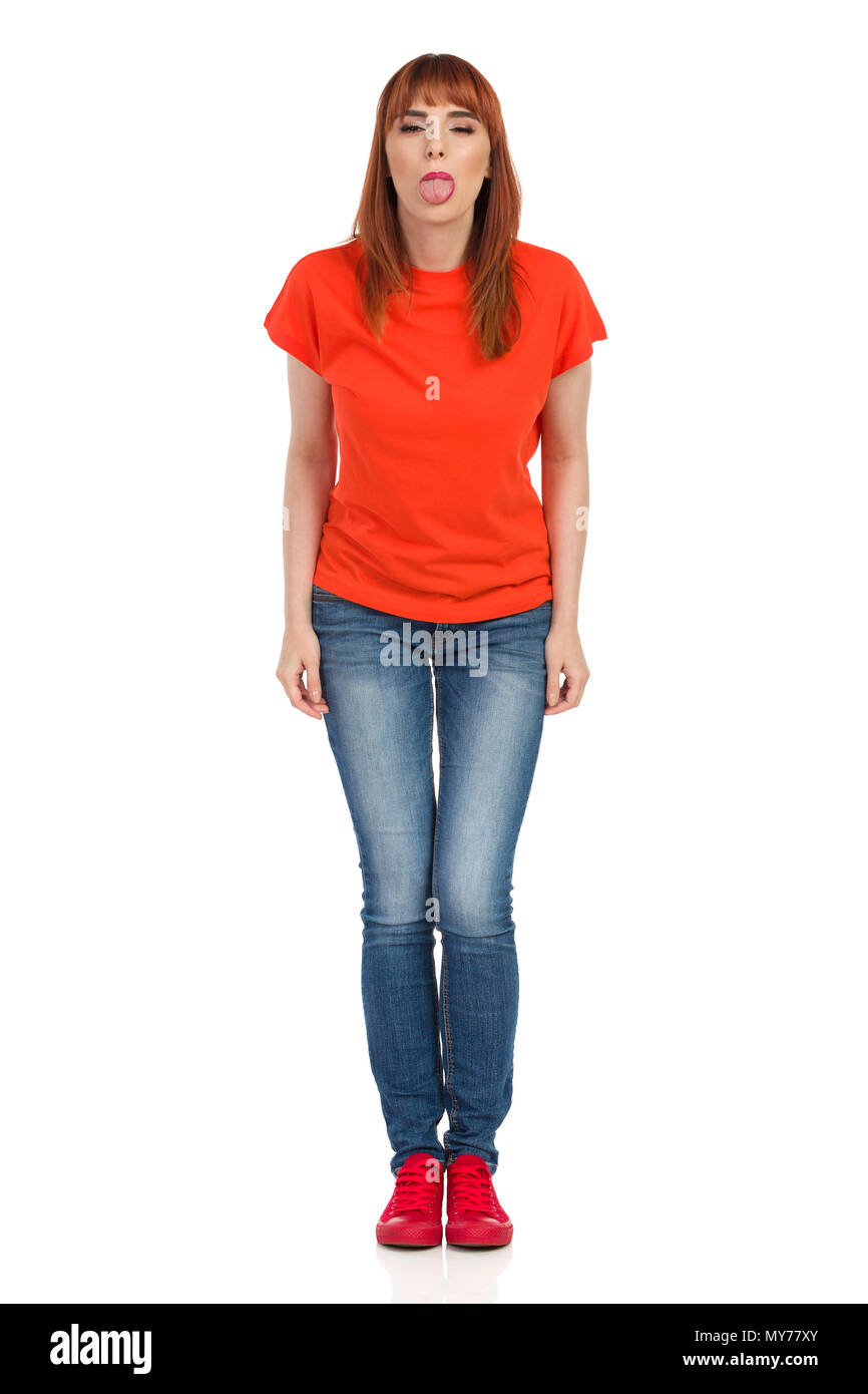 Young woman in orange t-shirt, jeans and red sneakers is standing