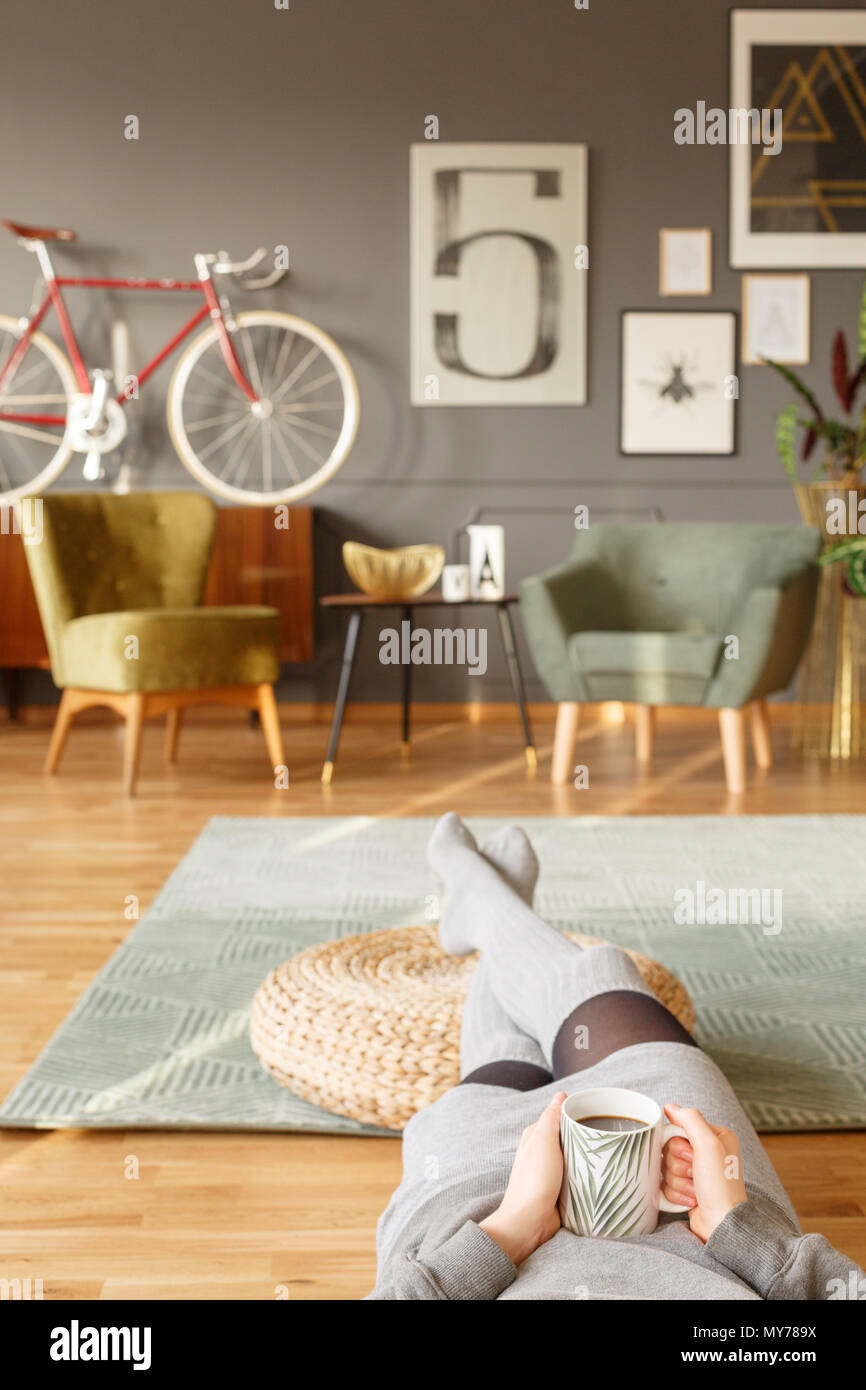 Young lady lying on a green carpet with a cup of tea in her hands and her legs on a pouf in a vintage living room interior with blurred background Stock Photo