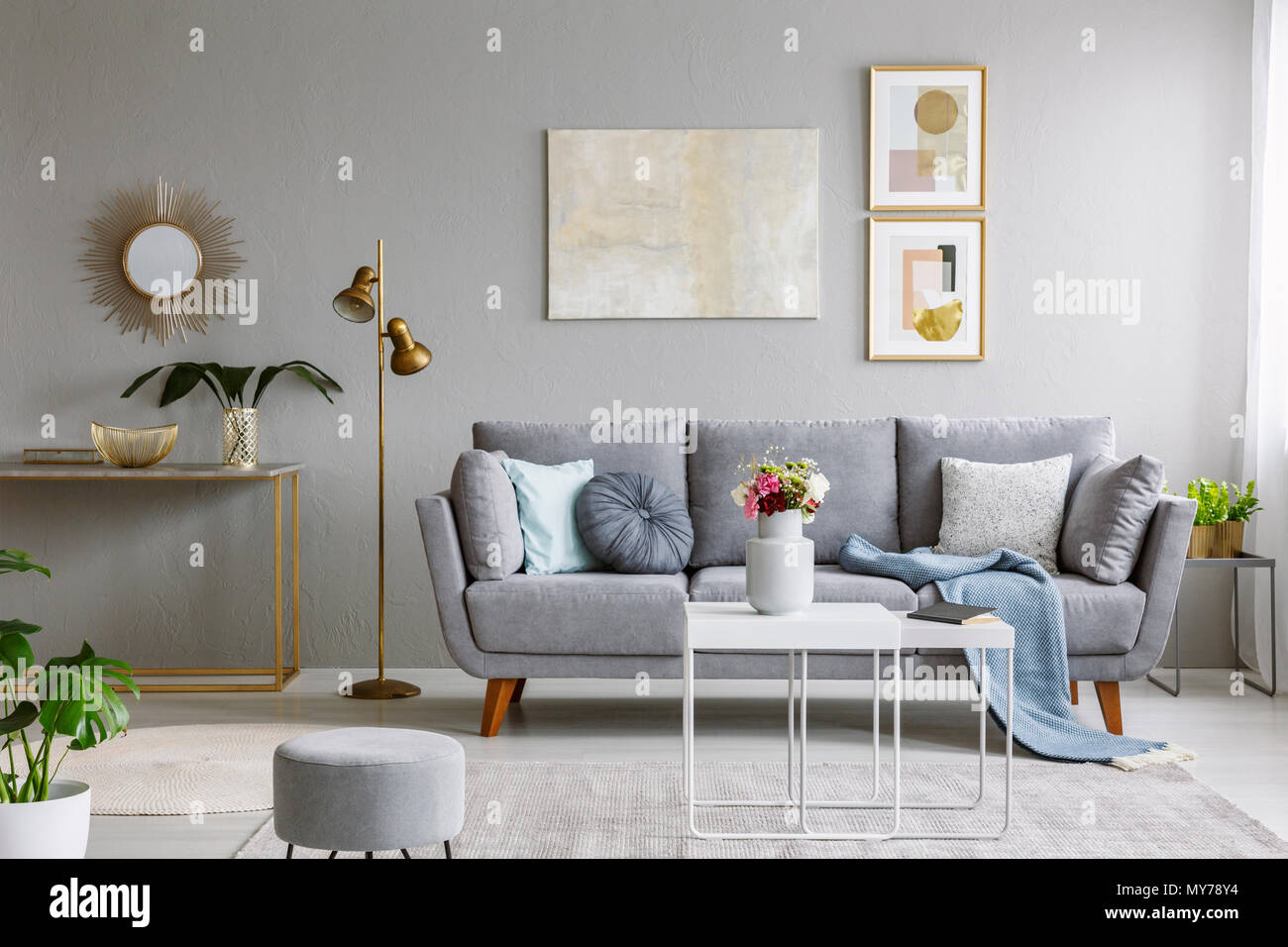Alamy & Real photo of a grey sofa with cushions and blanket standing in ...