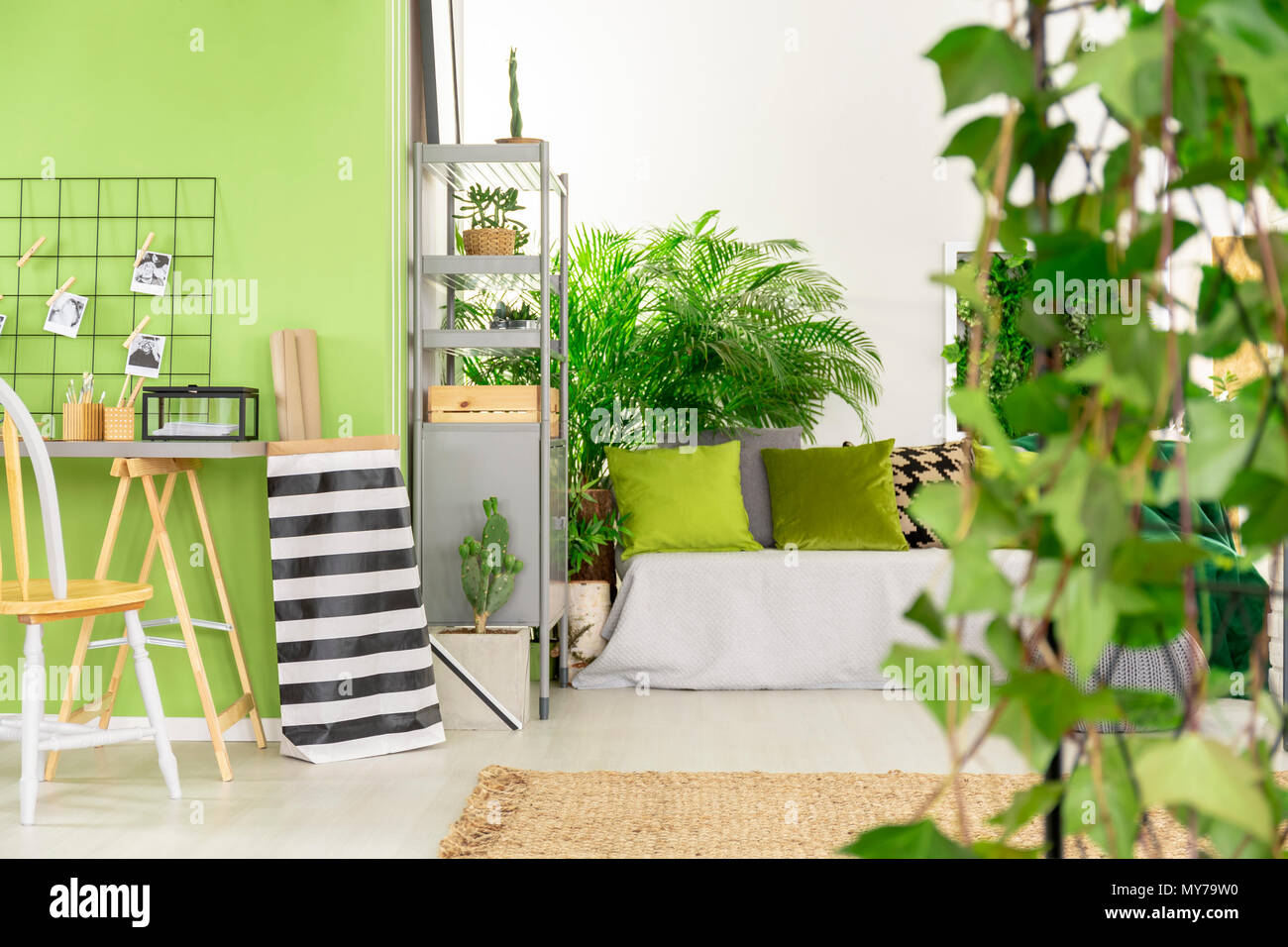 Striped bag next to desk and chair in green open space interior with pillows on bed. Real photo - Stock Image