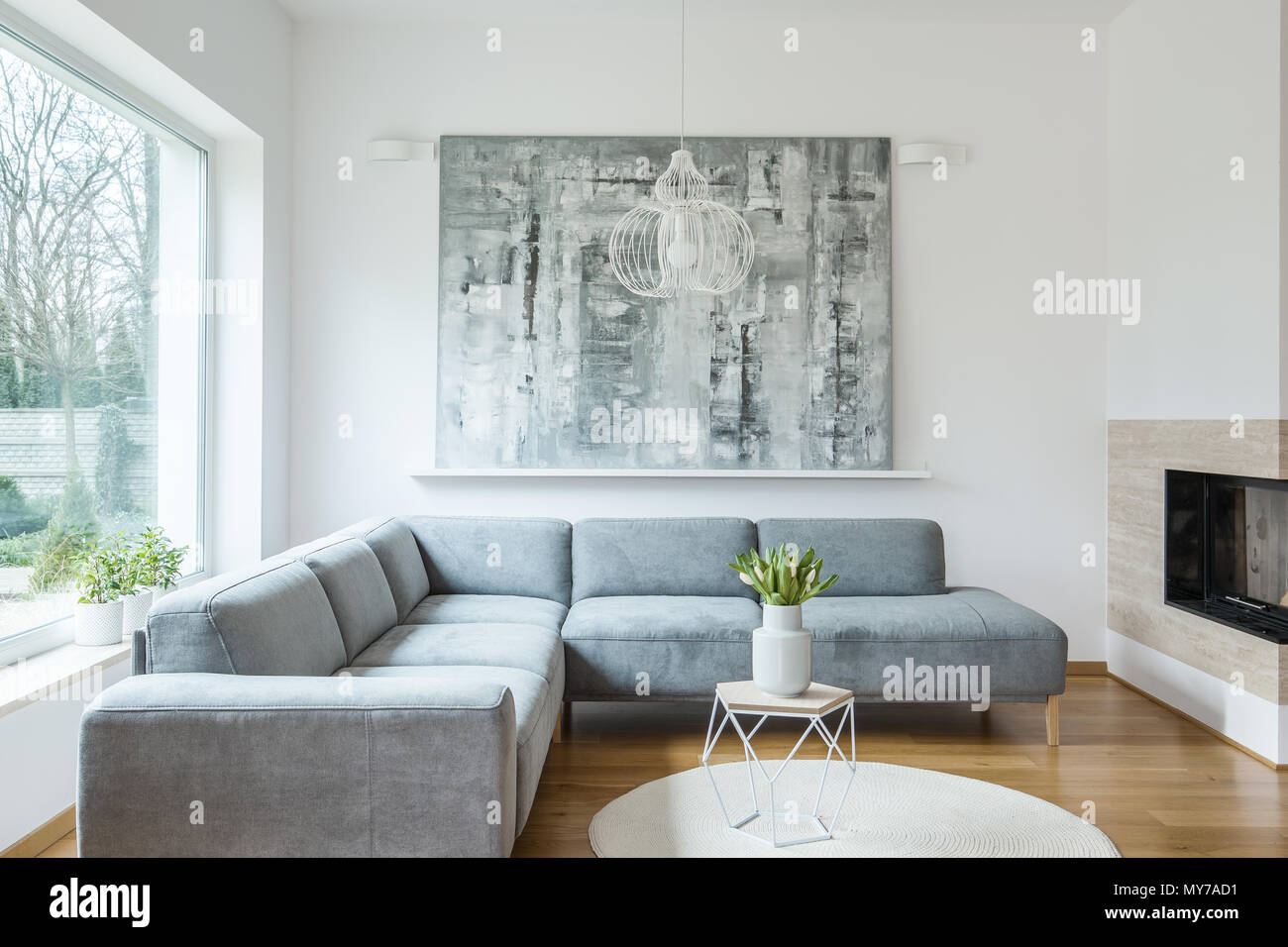 Grey corner sofa against white wall with painting in minimal living ...