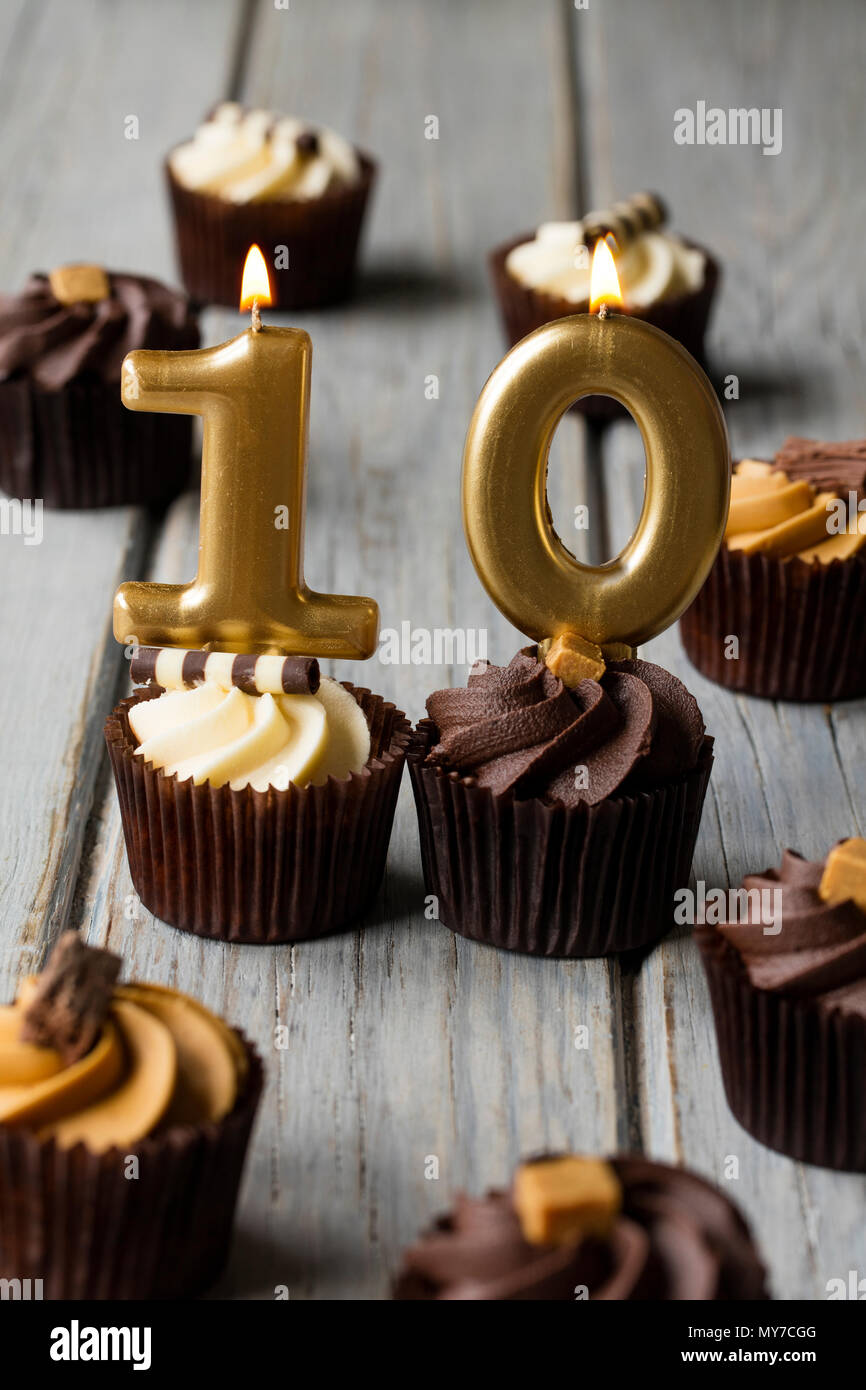Number 10 celebration birthday cupcakes on a wooden background - Stock Image