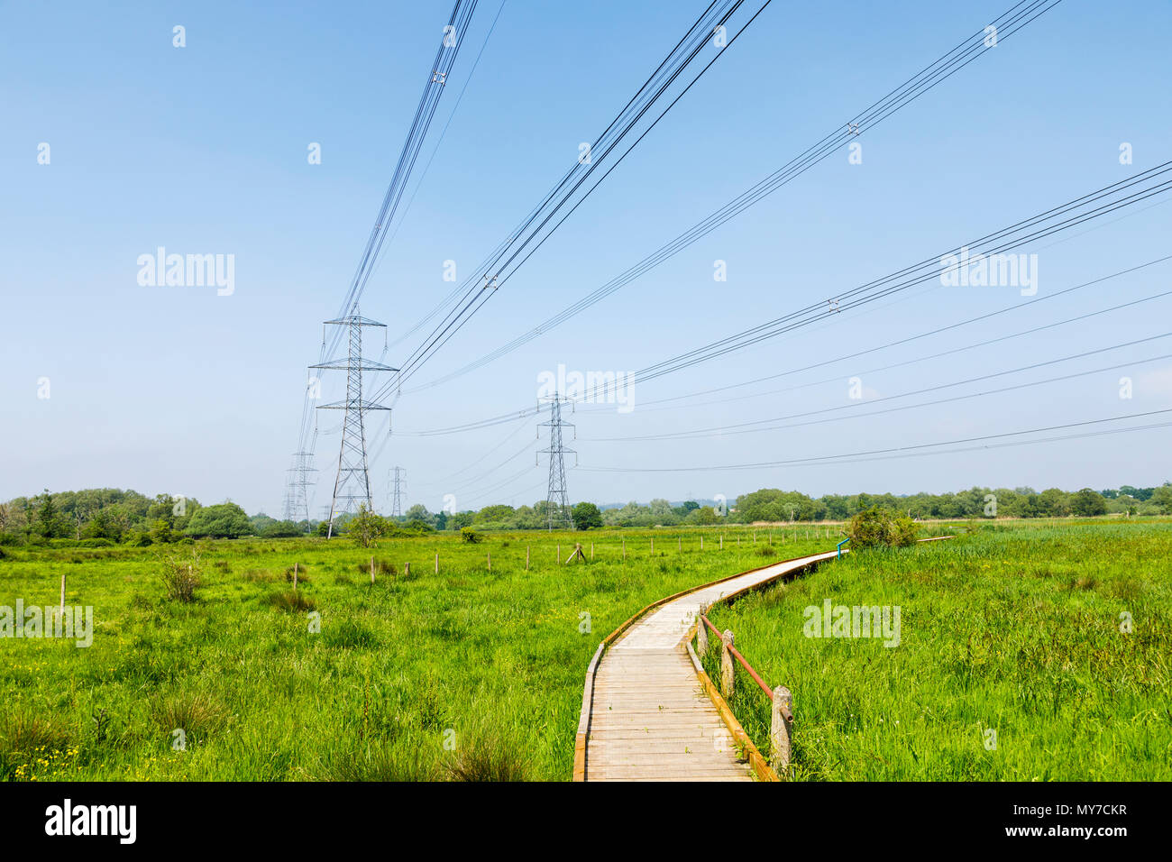Electricity pylons with overhead cables in the Lower Test Nature Reserve, Totton, River Test estuary, Redbridge, Southampton, Hampshire, UK - Stock Image