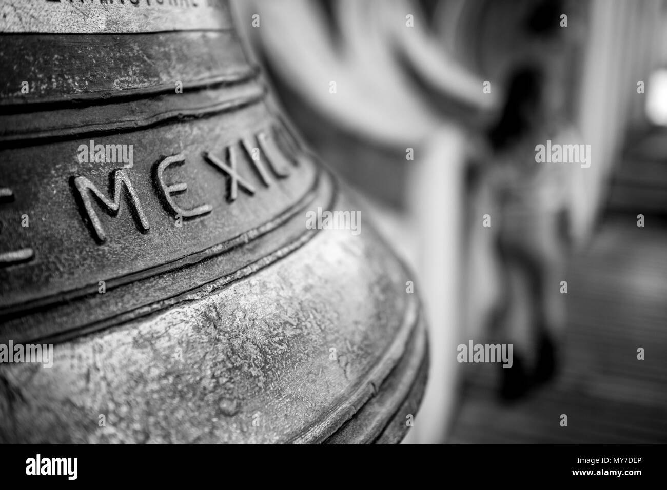 Letter M shallow focus on huge brass bell with caption Mexico with blurred child silhouette in the background in black and white - Stock Image
