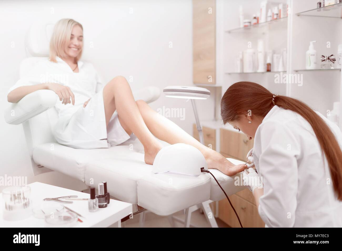 View of specialist in white working in beauty salon, making pedicure for pretty and young client in arm chair. Female professional cleaning cuticle ar - Stock Image