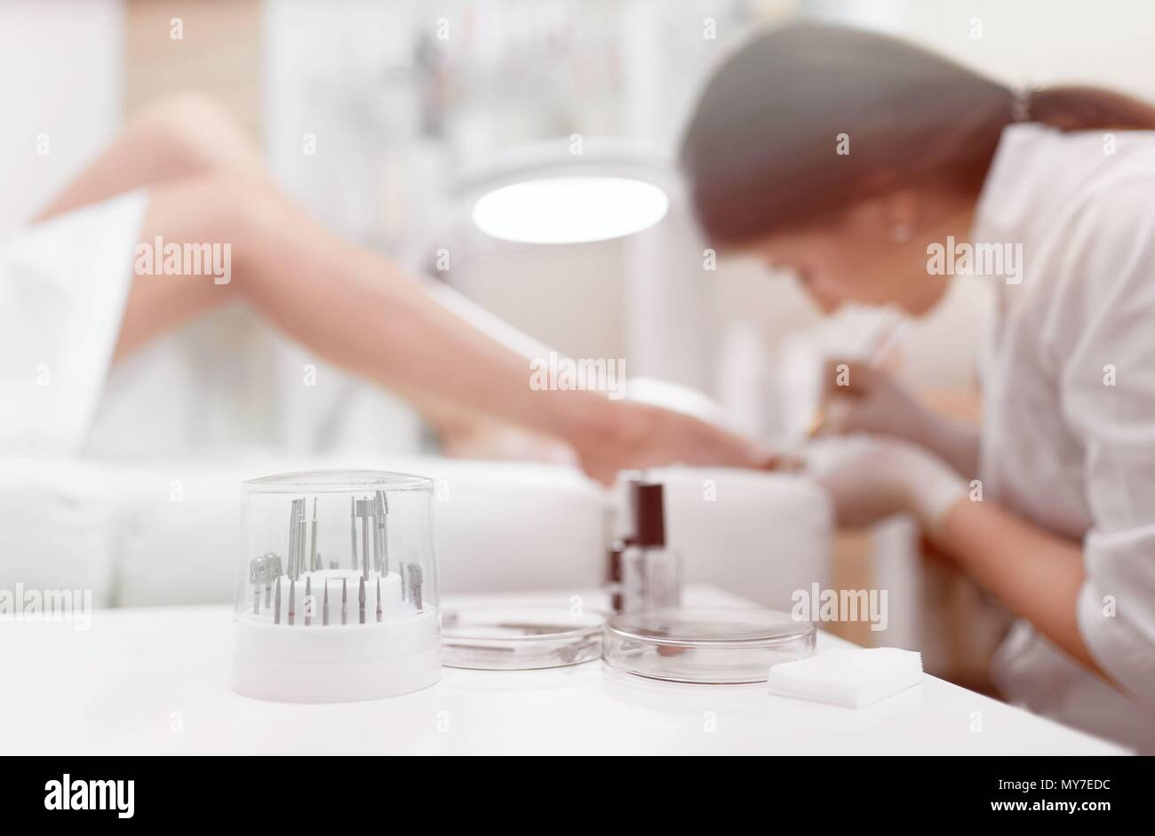 Close up of different professional cosmetics and oils, tools for french pedicure on white table. View from distance of specialist wearing gloves makin - Stock Image