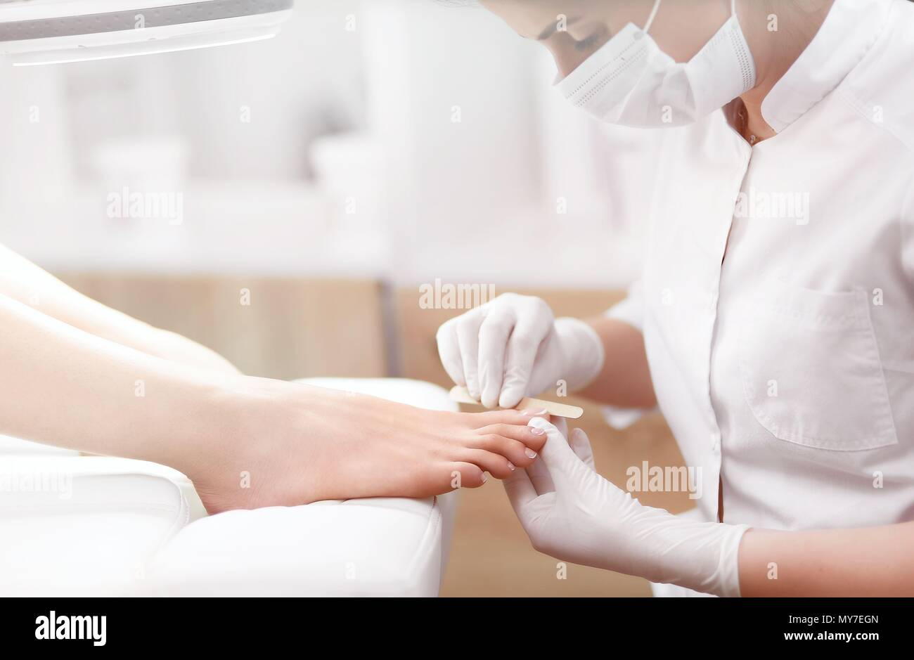 Nail artist in beauty salon making french pedicure for clients feet. Professional in mask on face polish nails by tool. Concept of nails, feet health  - Stock Image