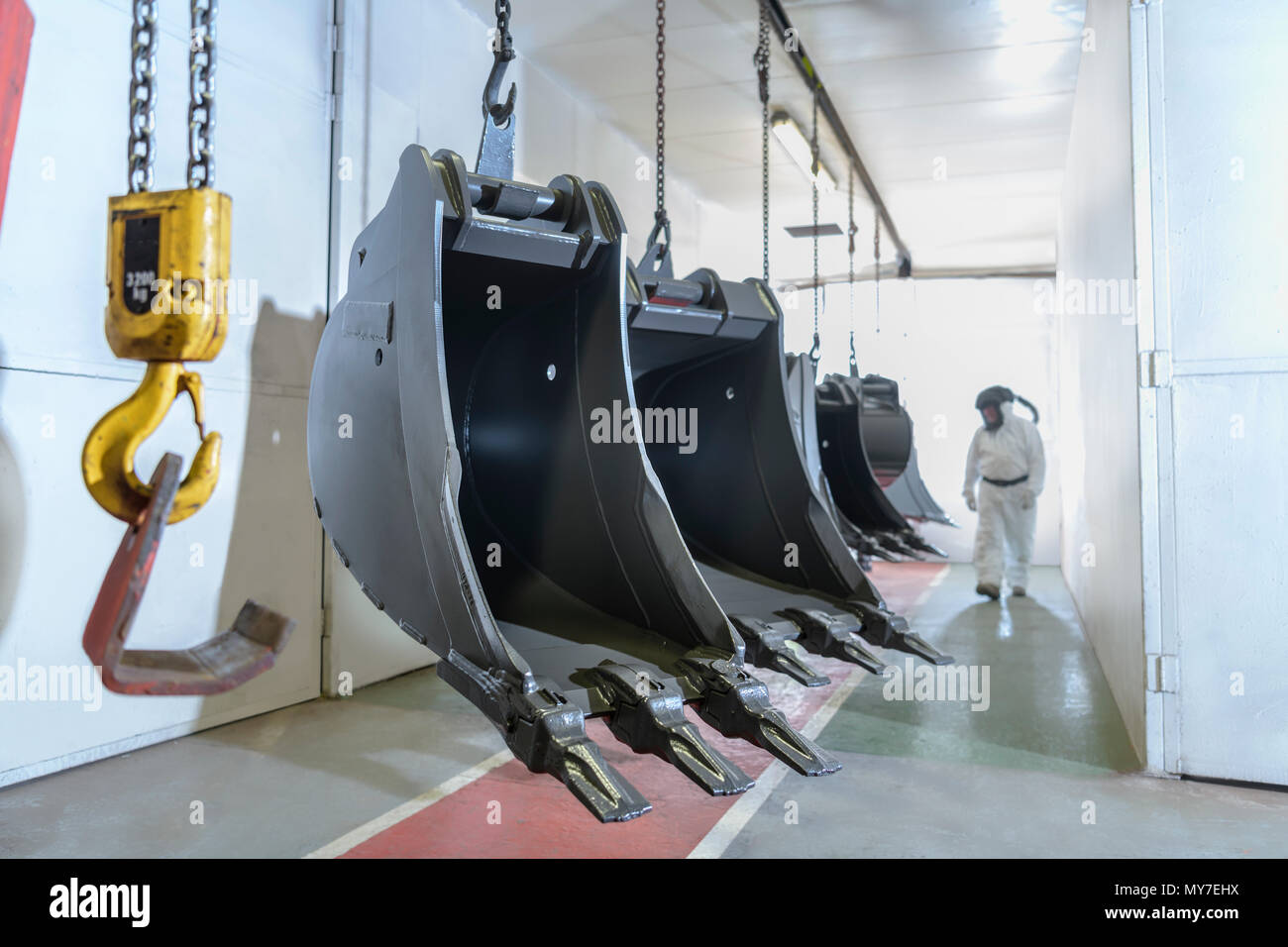 Spray painter checking painted digger buckets in engineering factory - Stock Image
