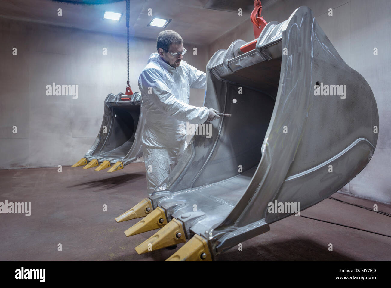 Spray painter cleaning digger bucket in spray booth in engineering factory - Stock Image